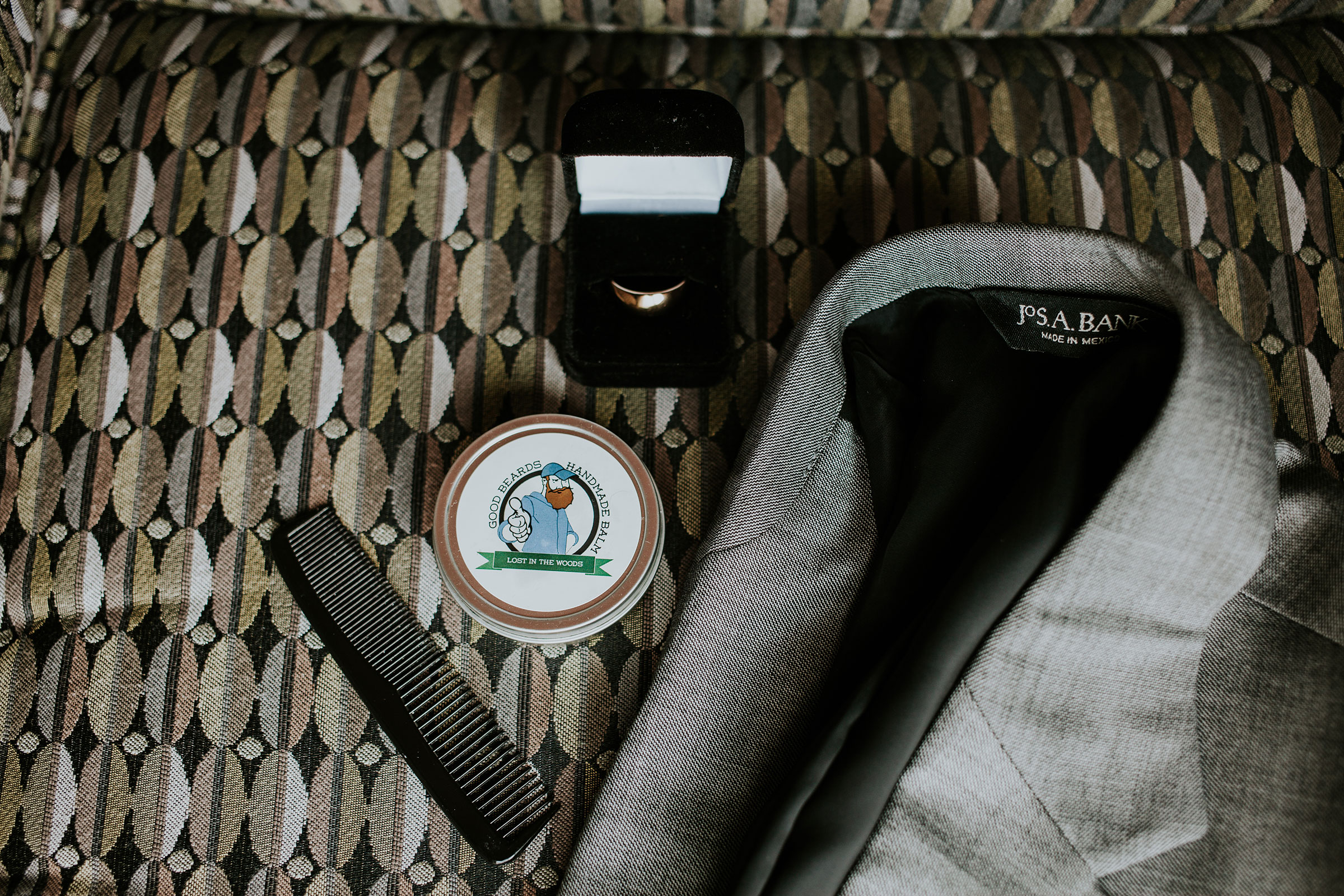 grooms-details-jacket-hair-product-and-ring-prairie-meadows-desmoines-iowa-raelyn-ramey-photography.jpg