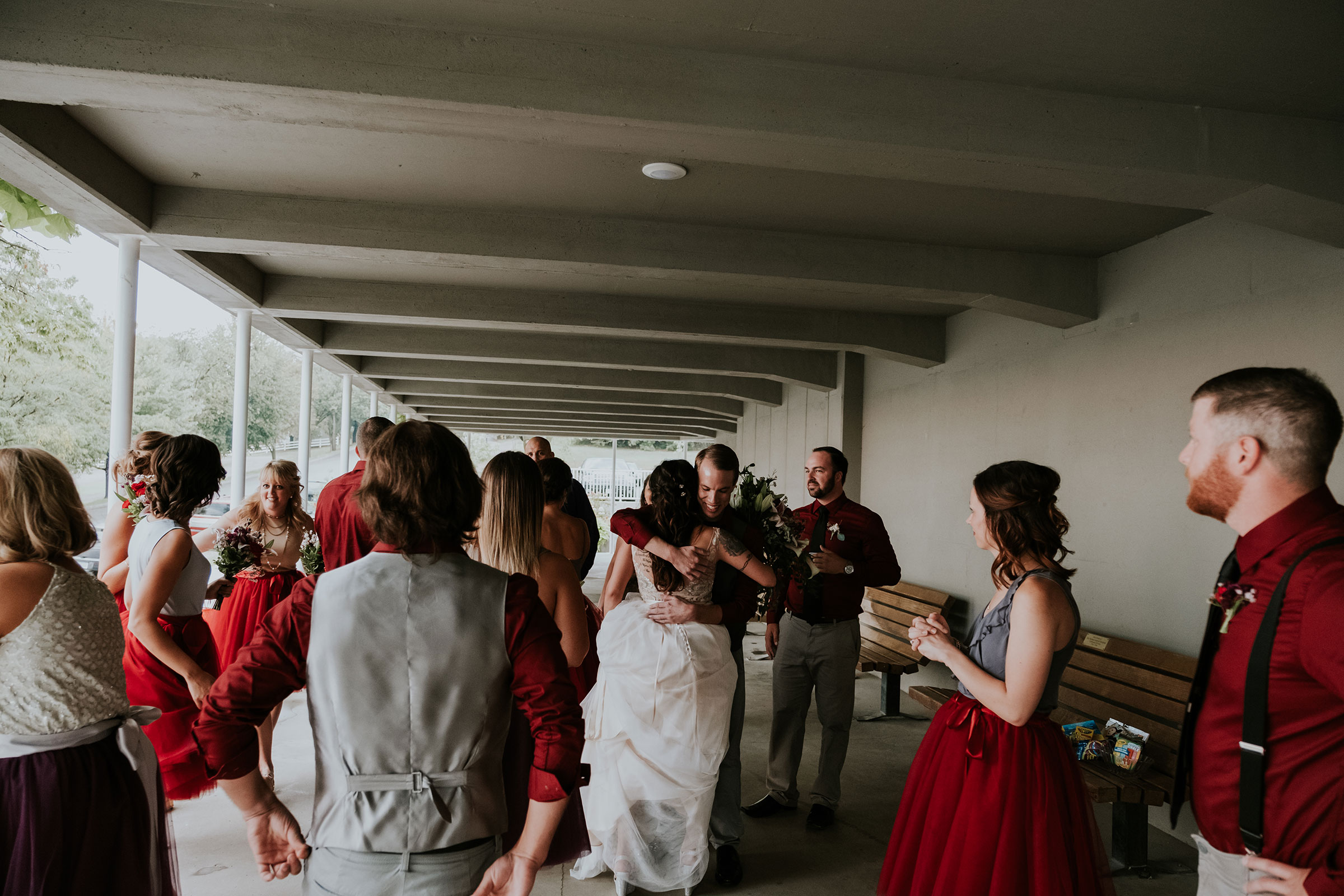 wedding-party-hugging-after-ceremony-pella-plaza-desmoines-iowa-raelyn-ramey-photography.jpg