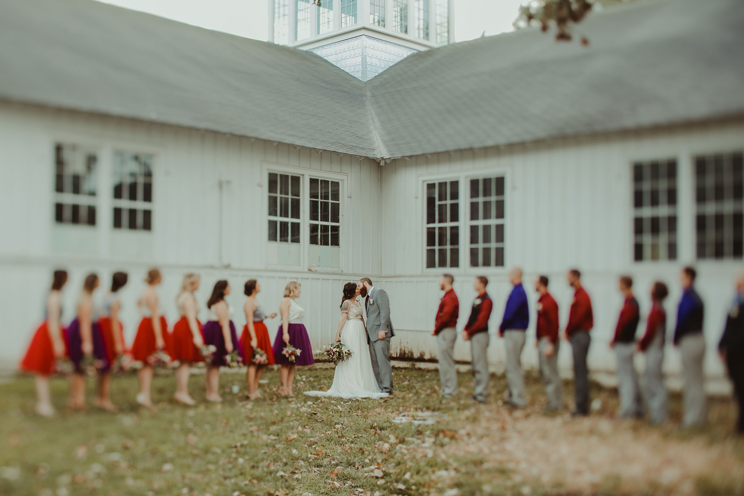 wedding-party-looking-at-bride-groom-kissing-iowa-state-fairgrounds-desmoines-iowa-raelyn-ramey-photography.jpg
