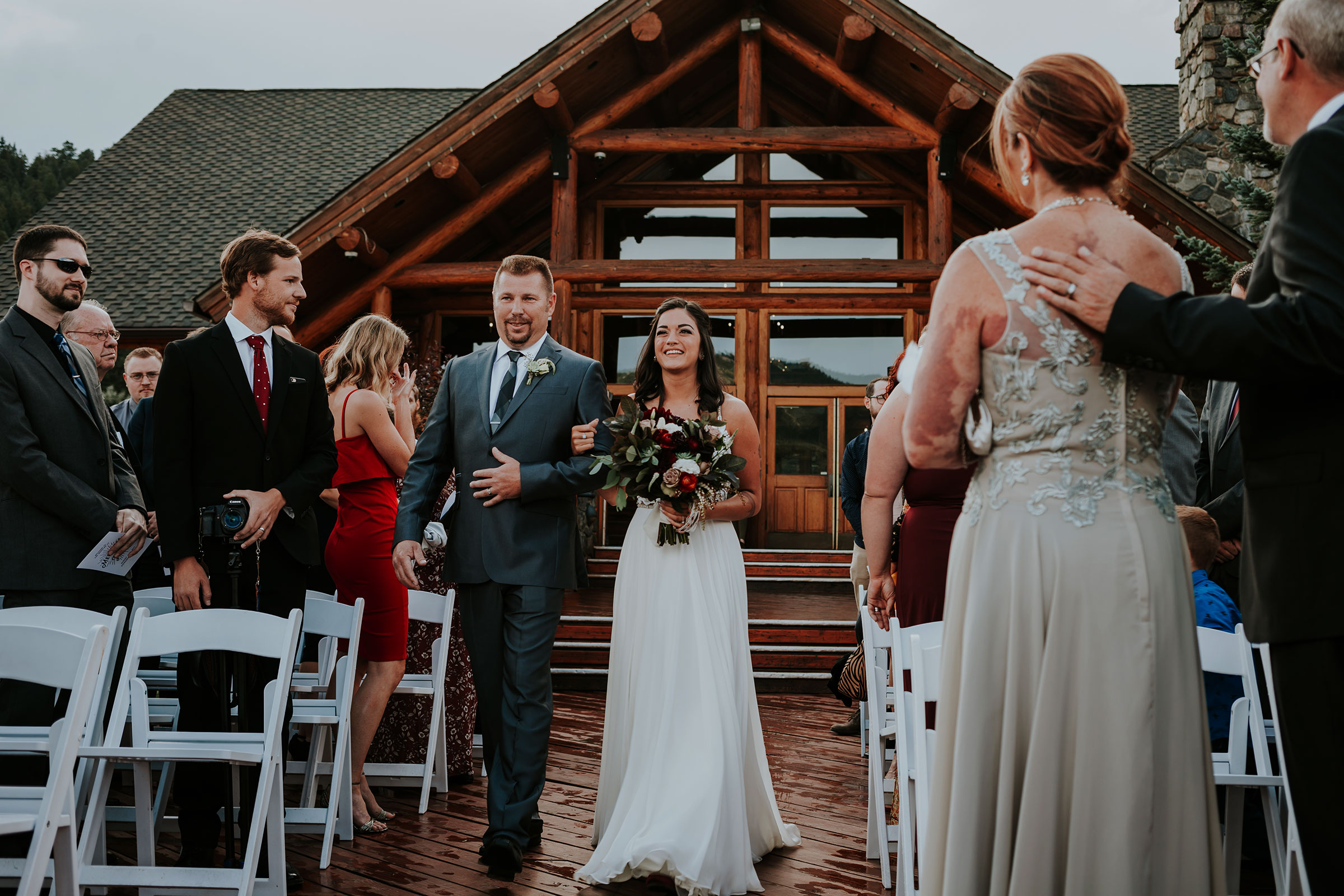 bride-walking-with-dad-down-aisle-in-front-of-lake-house-evergreen-lake-colorado.jpg