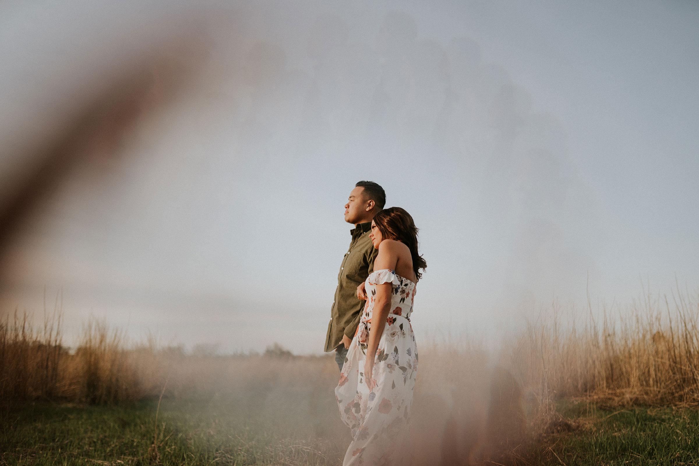 couple-looking-toward-sun-in-field-winterset-iowa-raelyn-ramey-photography.jpg