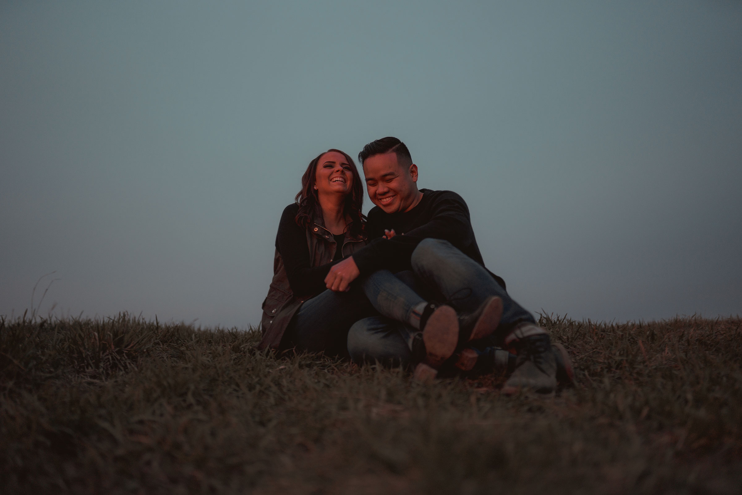 couple-sitting-on-hill-sunset-laughing-and-cuddling-winterset-iowa-raelyn-ramey-photography.jpg