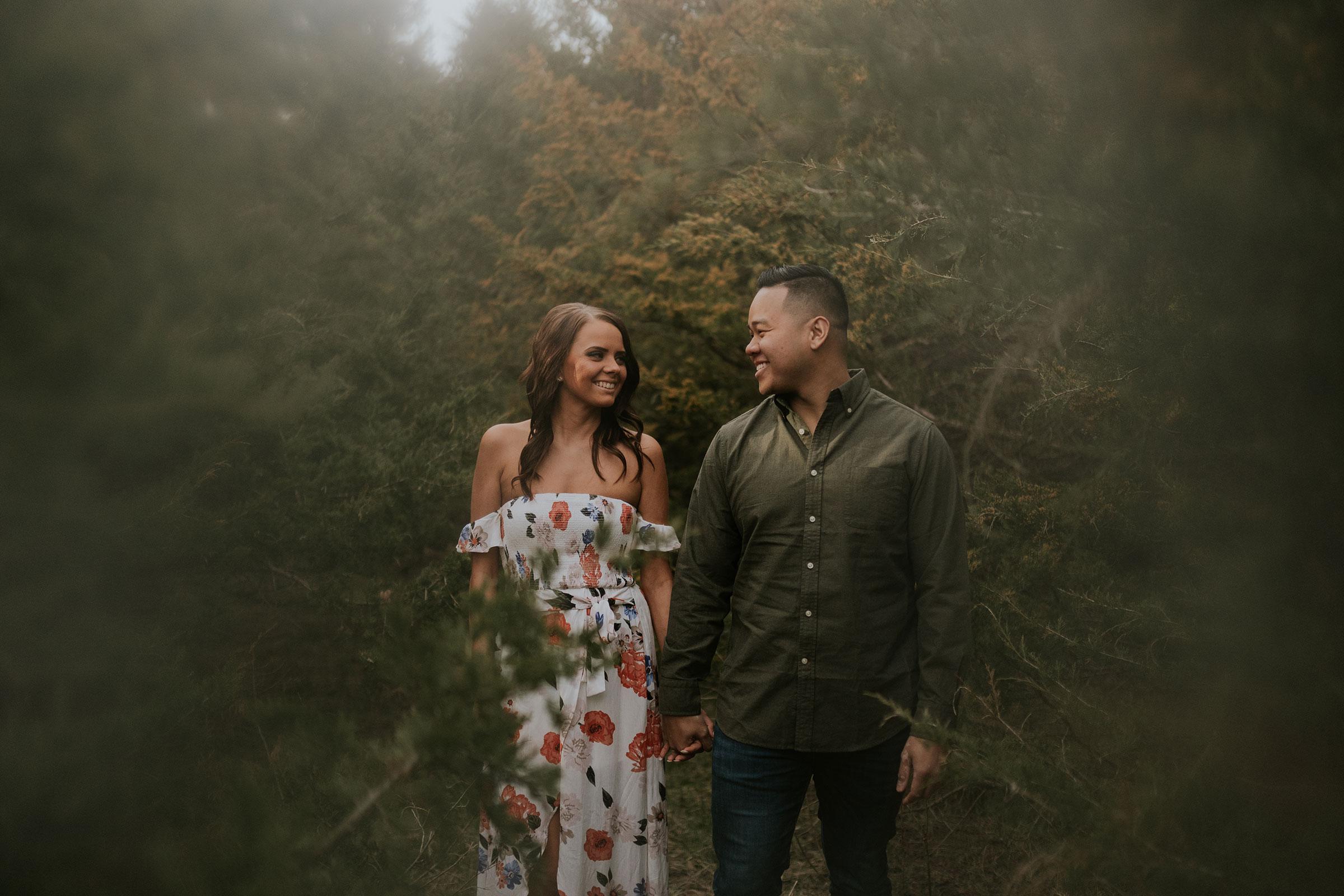 couple-standing-holding-hands-amongst-trees-iris-aisle-winterset-iowa-raelyn-ramey-photography.jpg