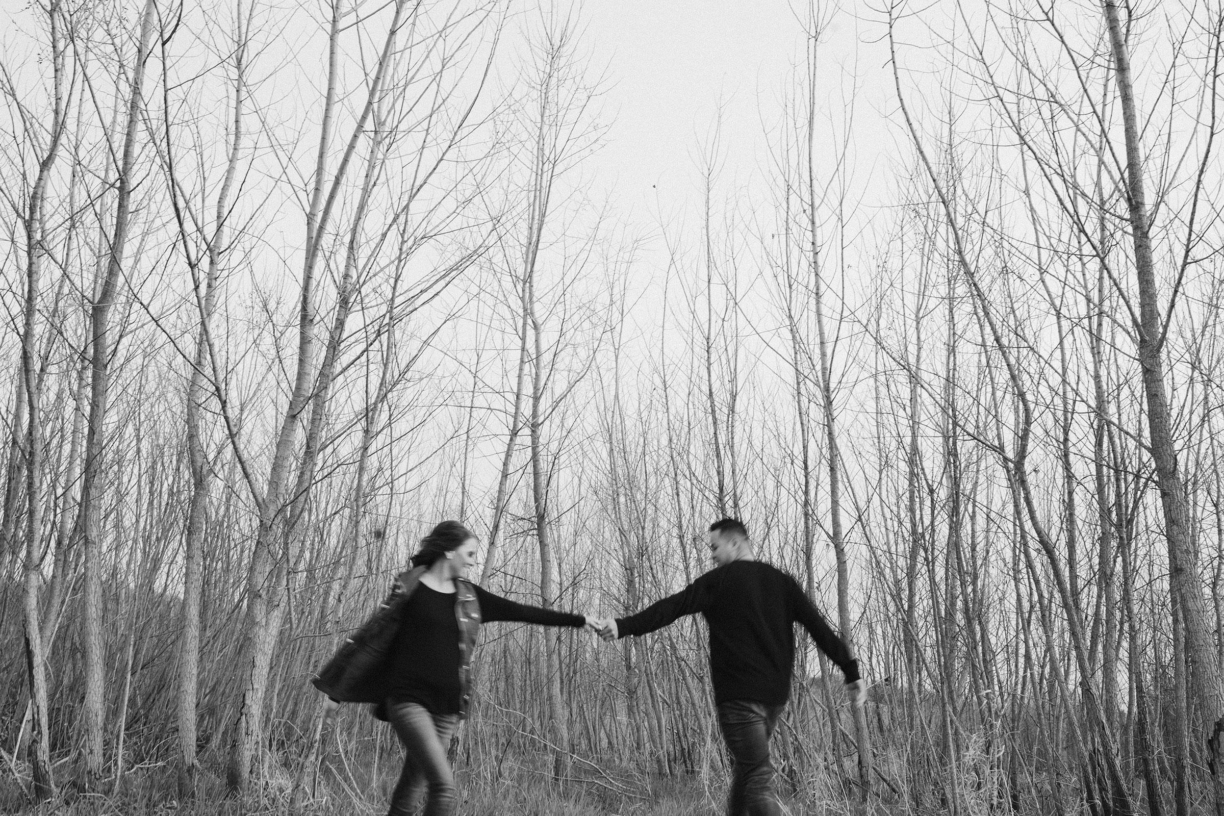 couple-walking-in-circles-in-woods-winterset-iowa-raelyn-ramey-photography.jpg