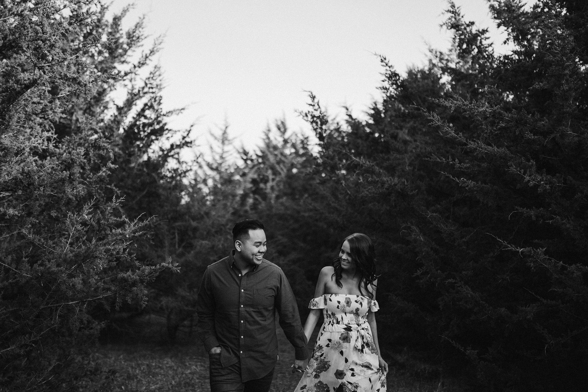 couple-walking-through-trees-iris-aisle-winterset-iowa-raelyn-ramey-photography.jpg