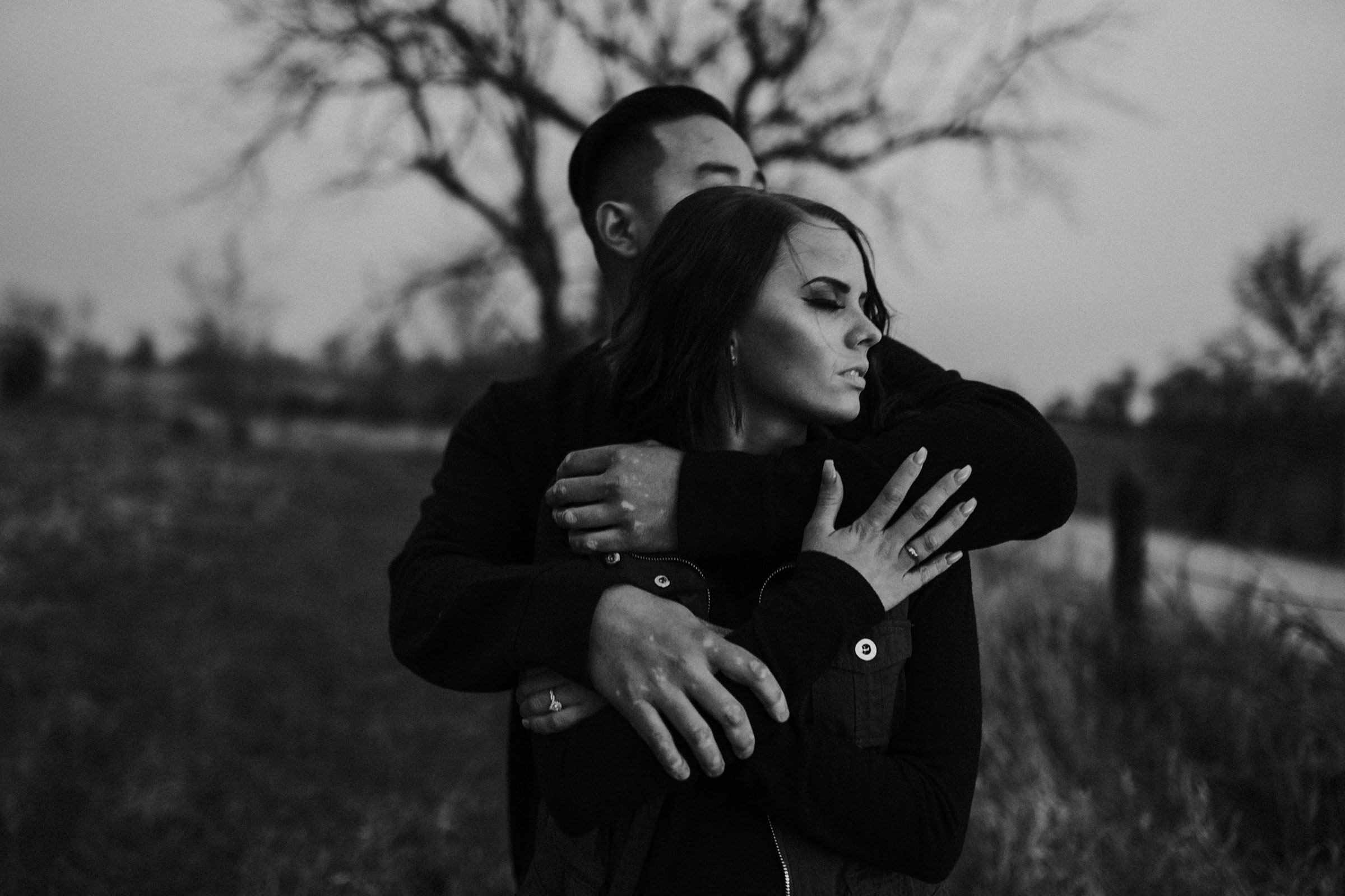 fiance-holding-each-other-while-looking-at-sunset-winterset-iowa-raelyn-ramey-photography.jpg