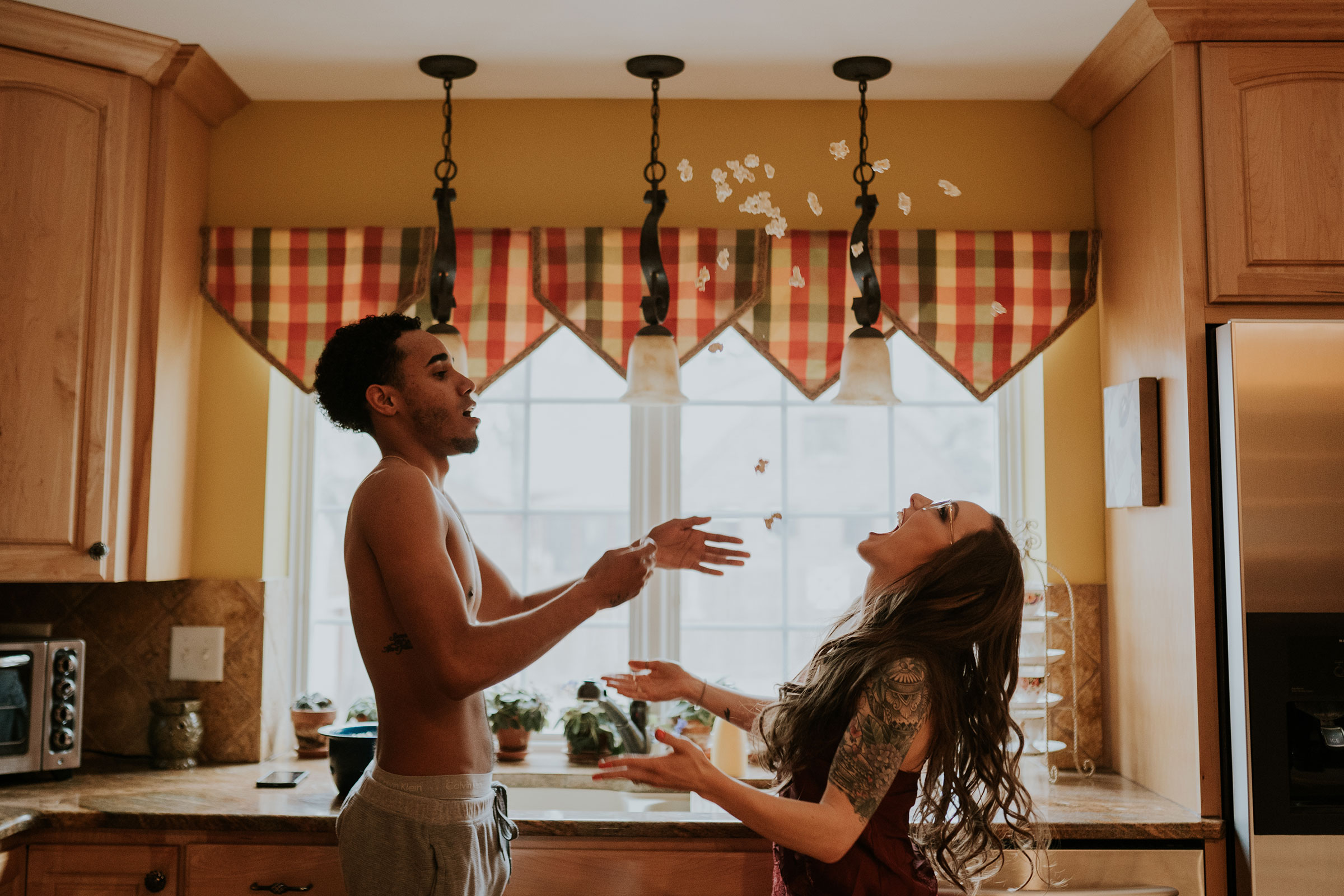 couple-playing-catch-with-popcorn-in-kitchen-engagement-desmoines-iowa-raelyn-ramey-photography.jpg
