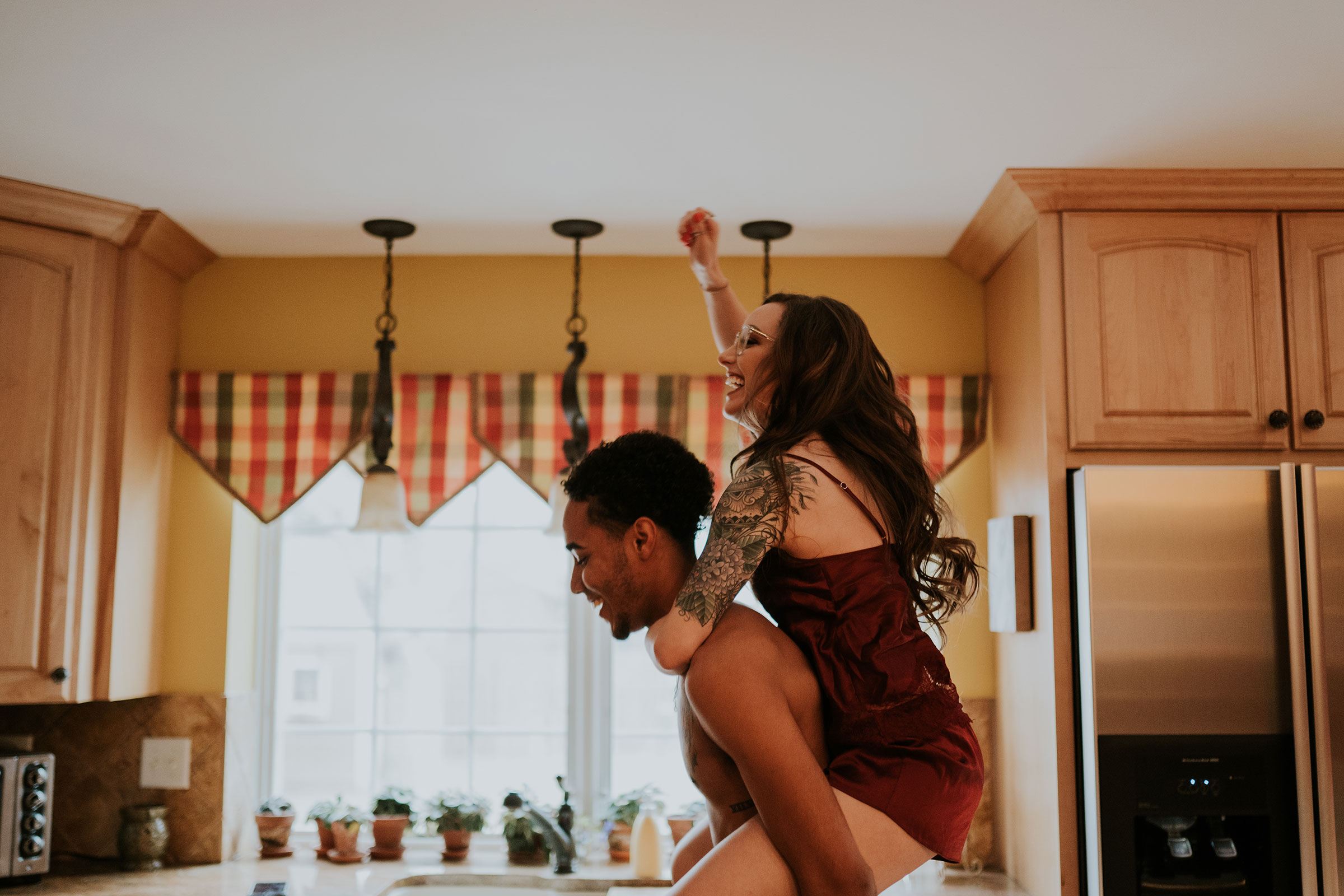 couple-playing-in-kitchen-laughing-engagement-desmoines-iowa-raelyn-ramey-photography.jpg