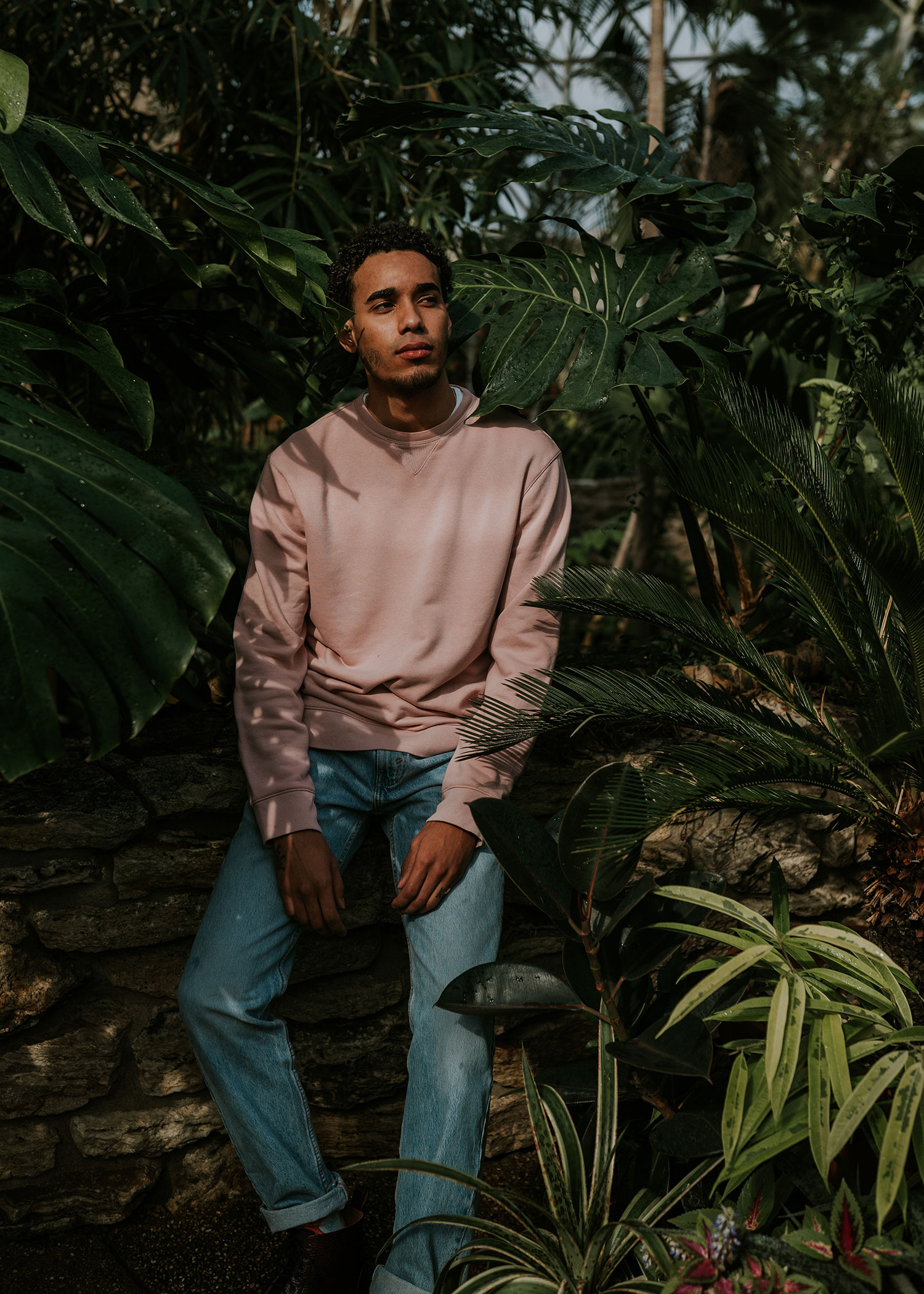 man-sitting-amongst-plants-botanical-gardens-engagement-desmoines-iowa-raelyn-ramey-photography.jpg
