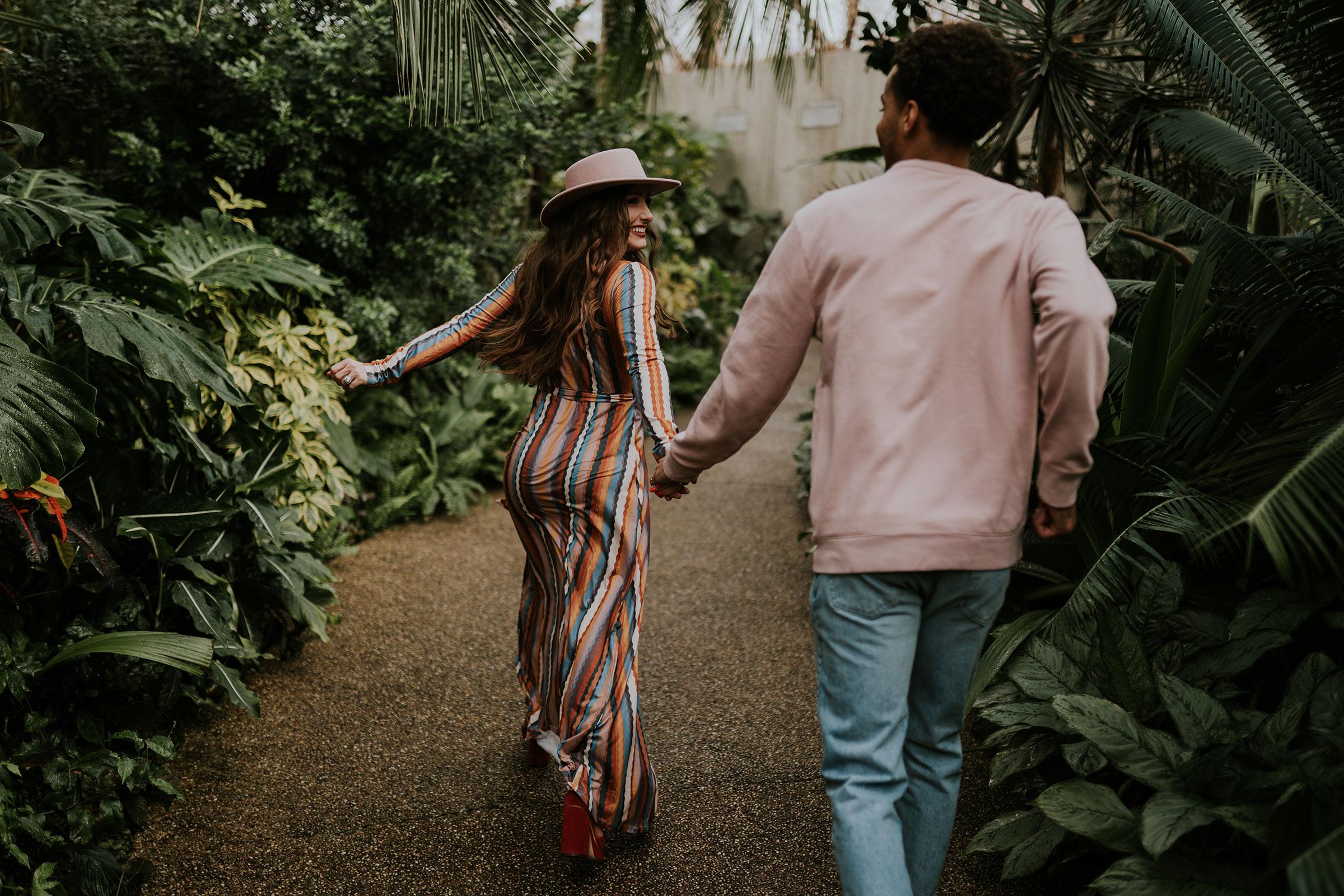 woman-and-man-running-through-botanical-gardens-engagement-desmoines-iowa-raelyn-ramey-photography.jpg