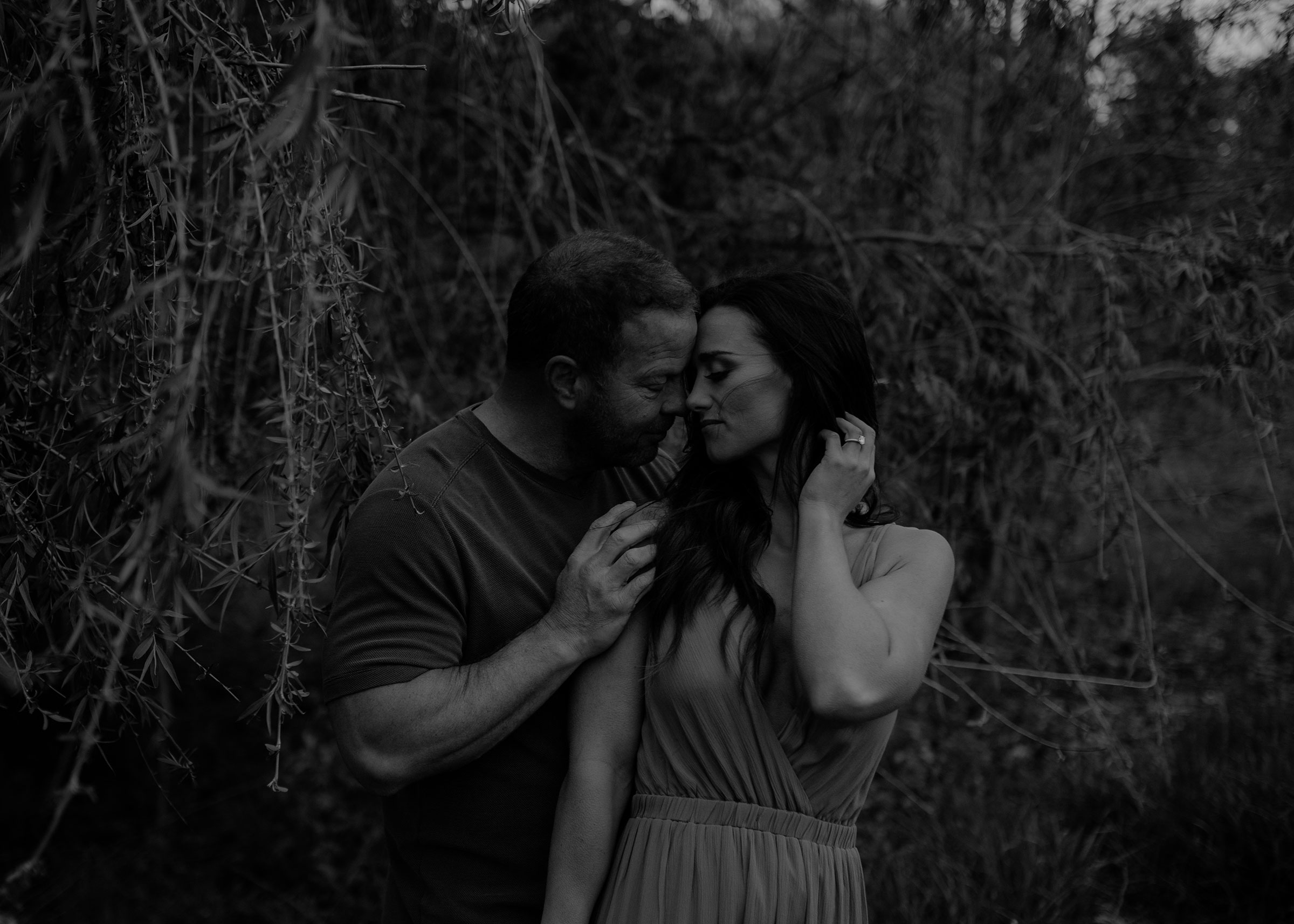 couple-holding-close-while-touching-engagement-desmoines-iowa-raelyn-ramey-photography.jpg