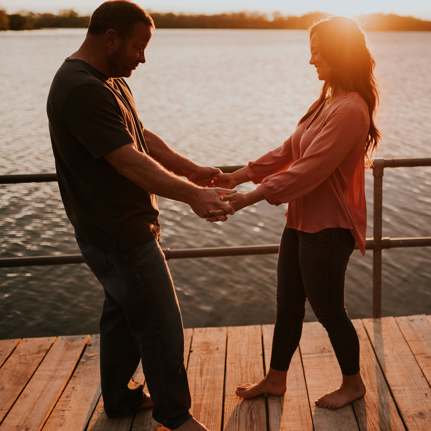 couple-holding-hands-dancing-on-dock-engagement-desmoines-iowa-raelyn-ramey-photography.jpg