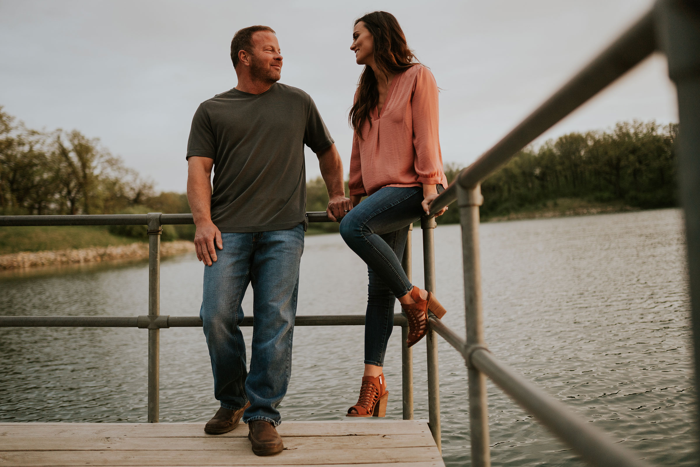 couple-leaning-on-dock-railing-looking-at-each-other-engagement-desmoines-iowa-raelyn-ramey-photography.jpg