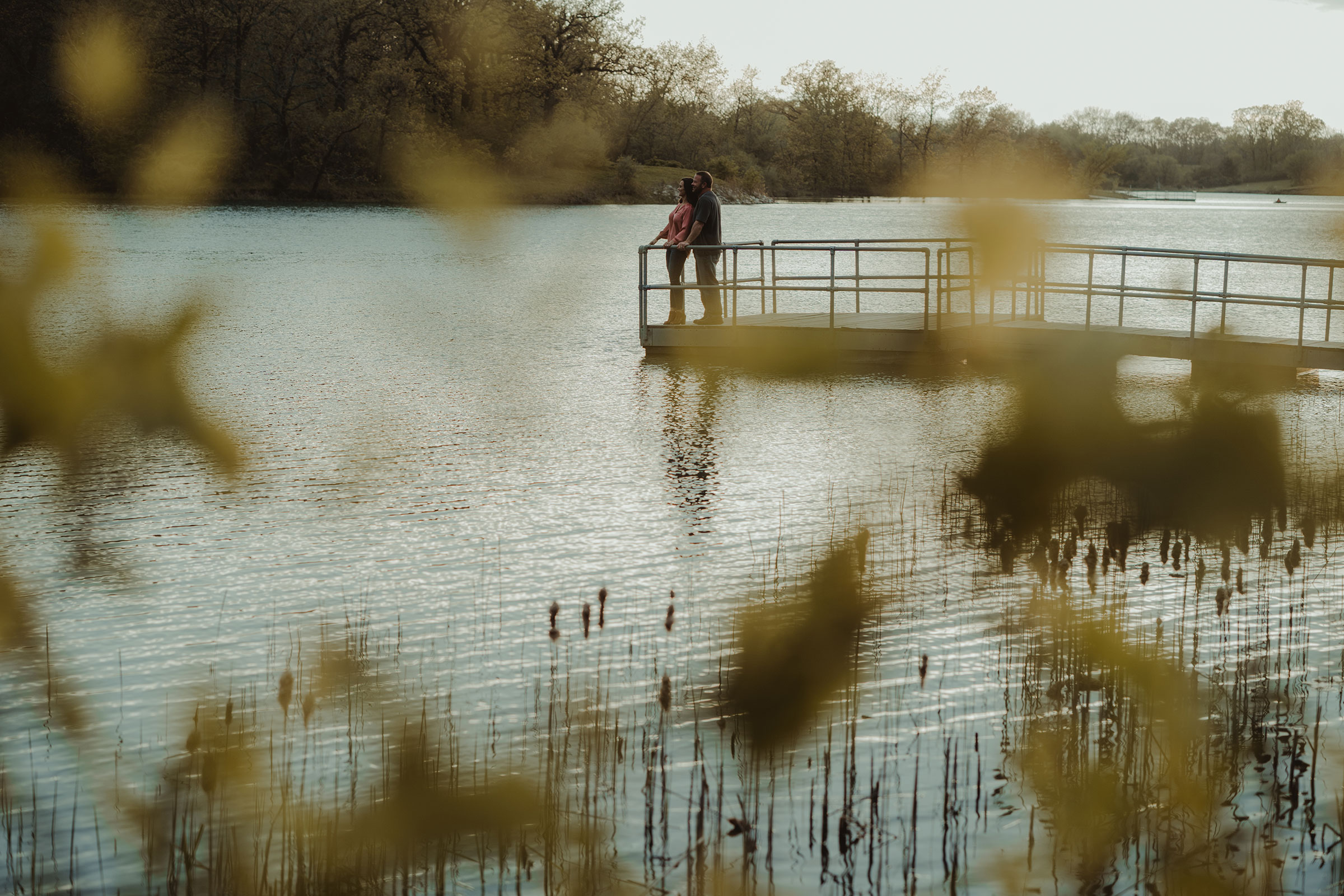 couple-looking-out-on-dock-at-water-while-holding-each-other-engagement-desmoines-iowa-raelyn-ramey-photography.jpg
