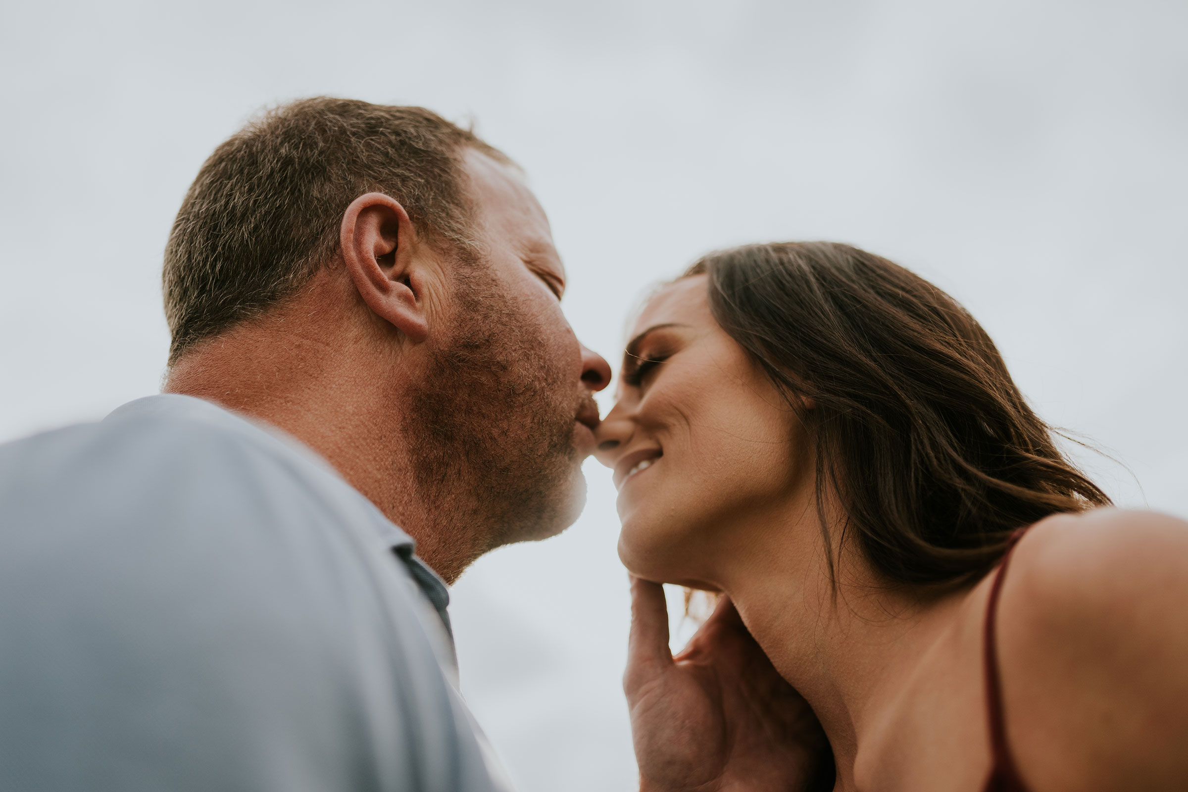 couple-smiling-and-kissing-nose-in-sun-light-engagement-desmoines-iowa-raelyn-ramey-photography.jpg