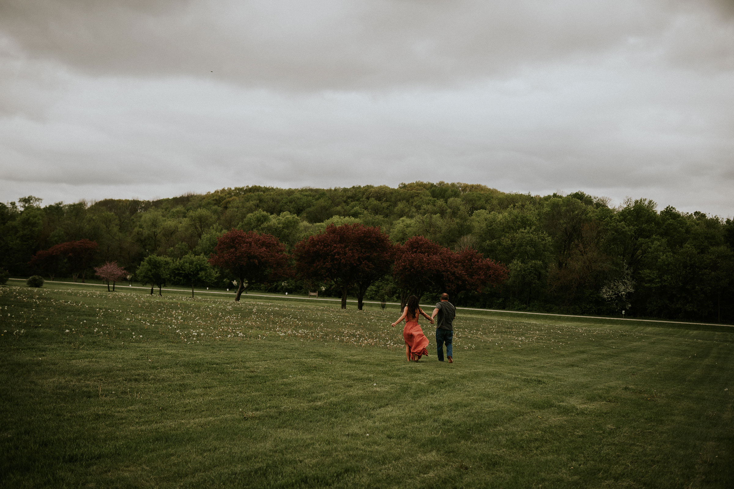 couple-running-through-grass-to-trees-engagement-desmoines-iowa-raelyn-ramey-photography.jpg