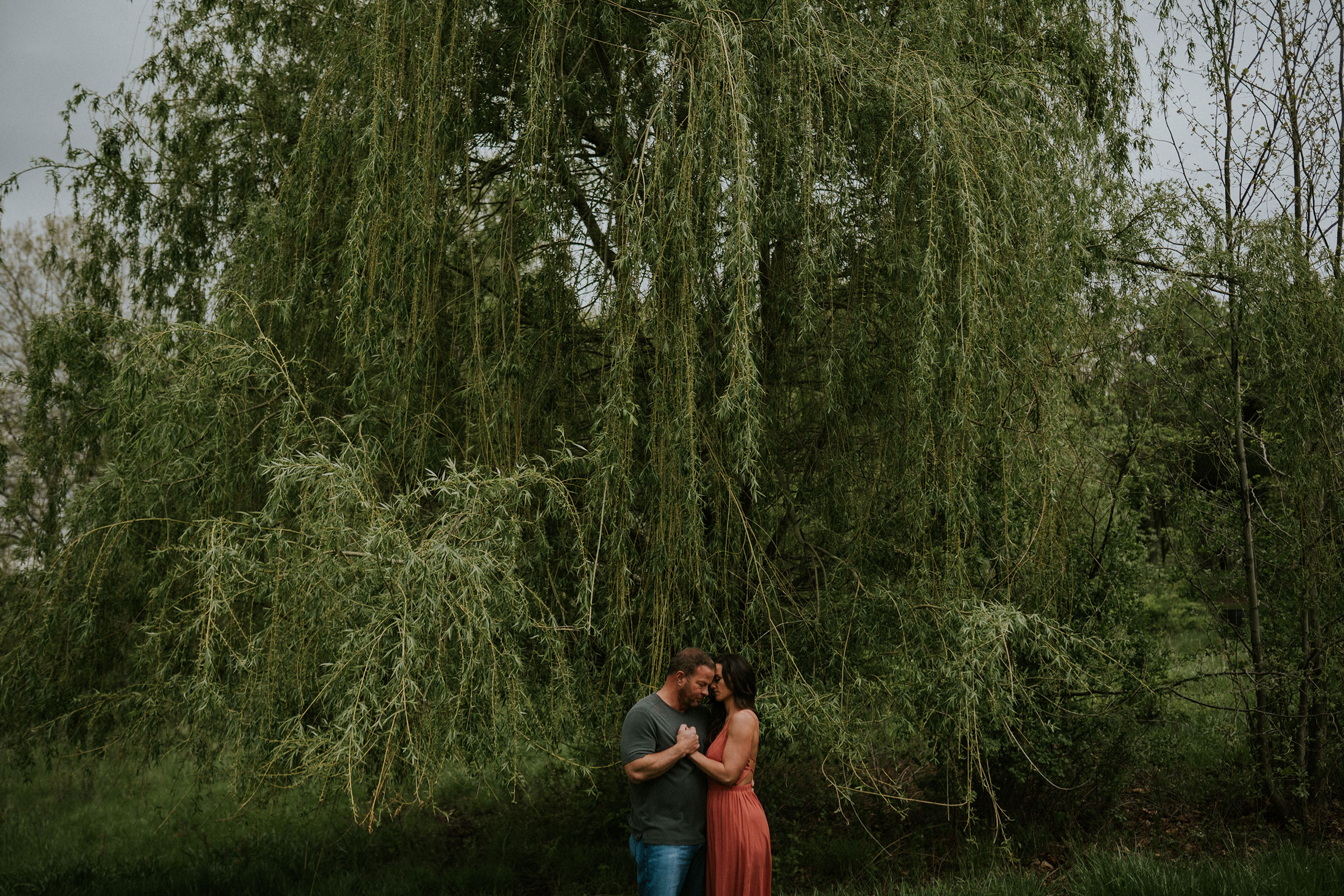 couple-standing-in-front-of-willow-tree-engagement-desmoines-iowa-raelyn-ramey-photography.jpg