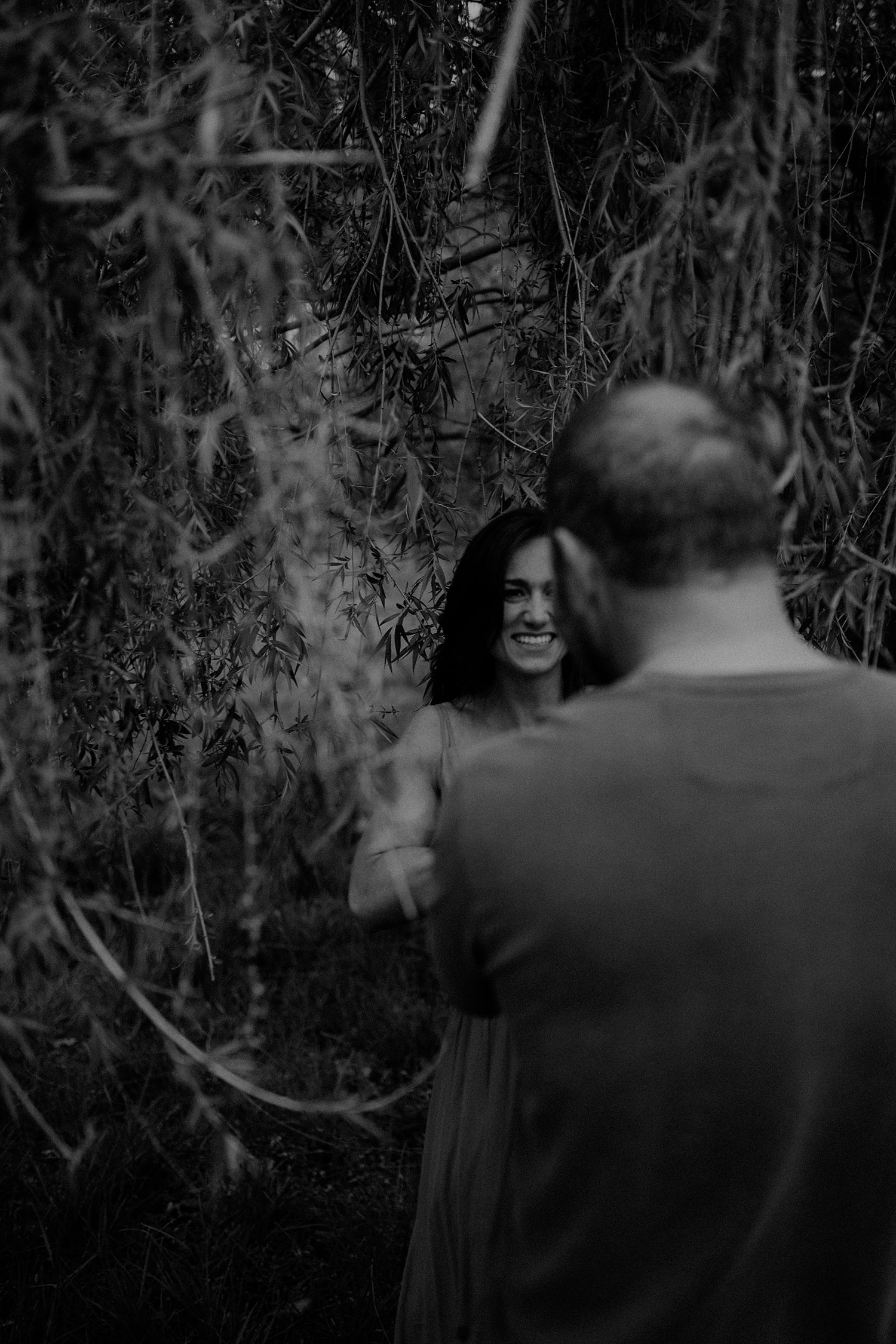 woman-leading-man-under-willow-tree-engagement-desmoines-iowa-raelyn-ramey-photography.jpg