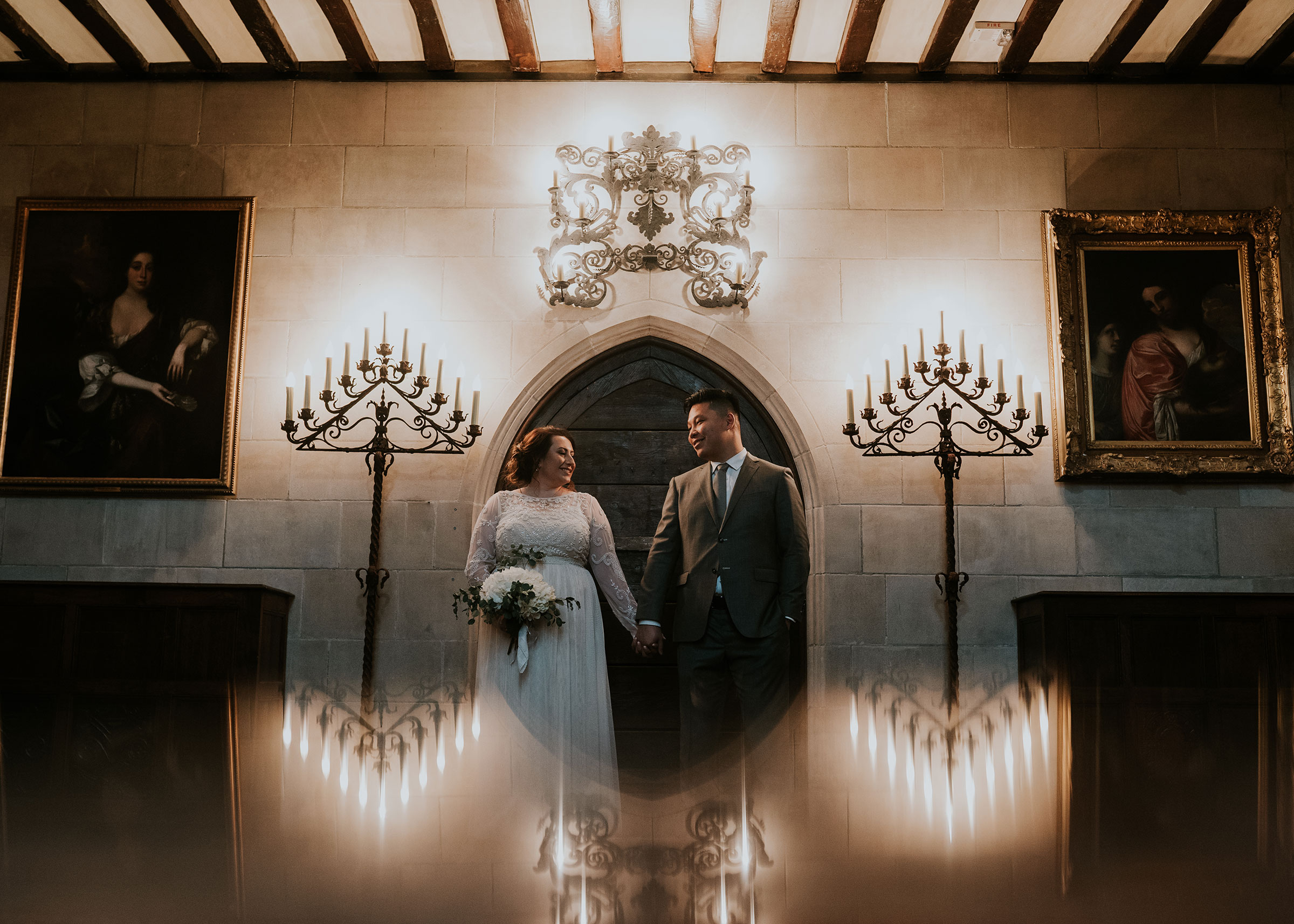 bride-groom-holding-hands-standing-in-front-of-arched-doors-and-candelabras-wedding-salisbury-house-desmoines-iowa-raelyn-ramey-photography.jpg
