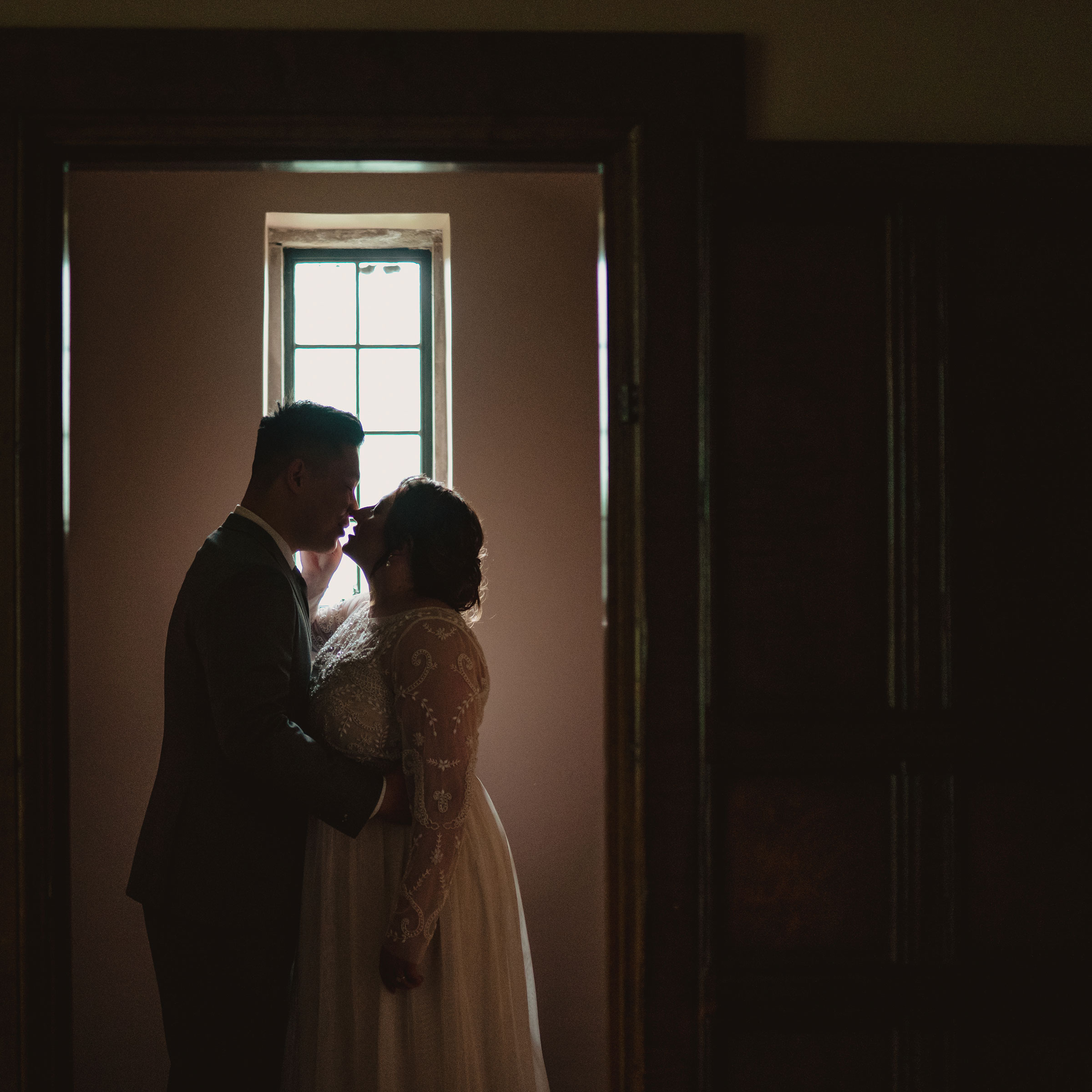 bride-groom-kissing-in-small-room-through-door-wedding-salisbury-house-desmoines-iowa-raelyn-ramey-photography.jpg