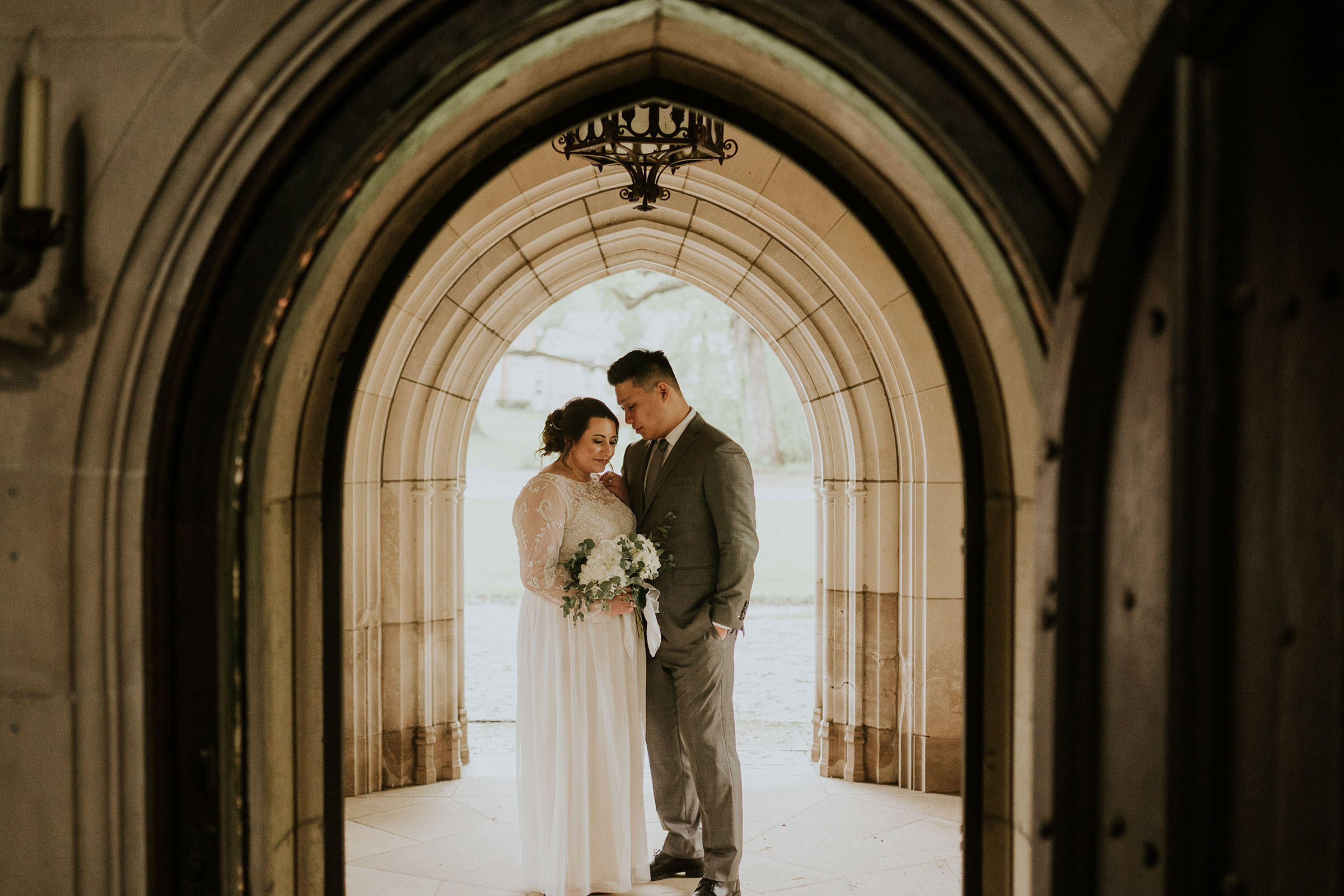 bride-groom-standing-under-arch-looking-at-each-other-wedding-salisbury-house-desmoines-iowa-raelyn-ramey-photography.jpg