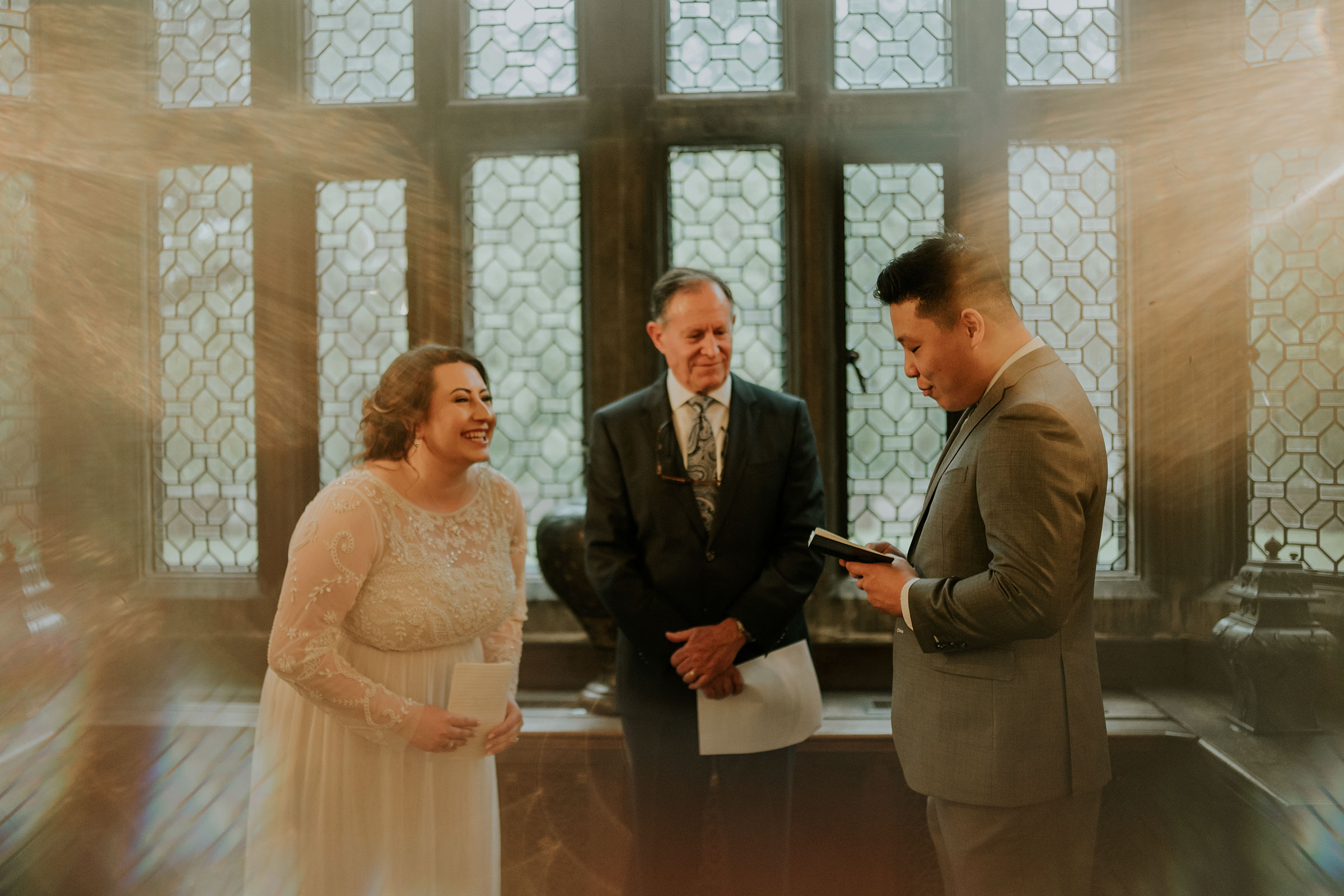 bride-laughing-during-groom-vows-elopement-salisbury-house-desmoines-iowa-raelyn-ramey-photography.jpg