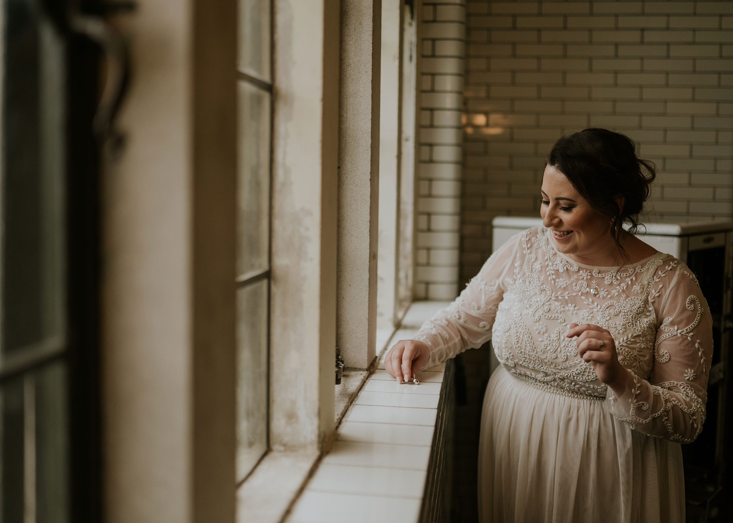 bride-laughing-putting-on-earrings-elopement-salisbury-house-desmoines-iowa-raelyn-ramey-photography.jpg
