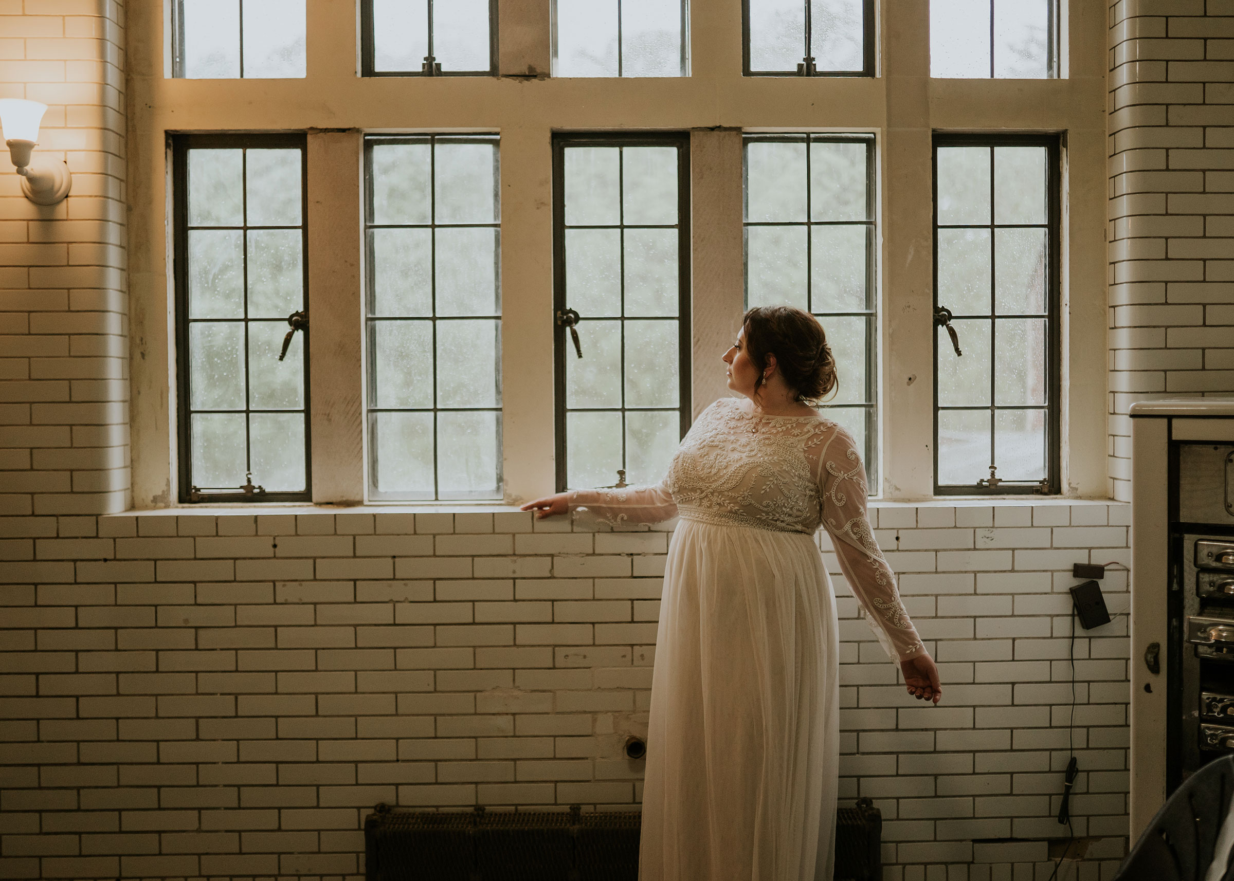 bride-posing-by-windows-elopement-salisbury-house-desmoines-iowa-raelyn-ramey-photography.jpg
