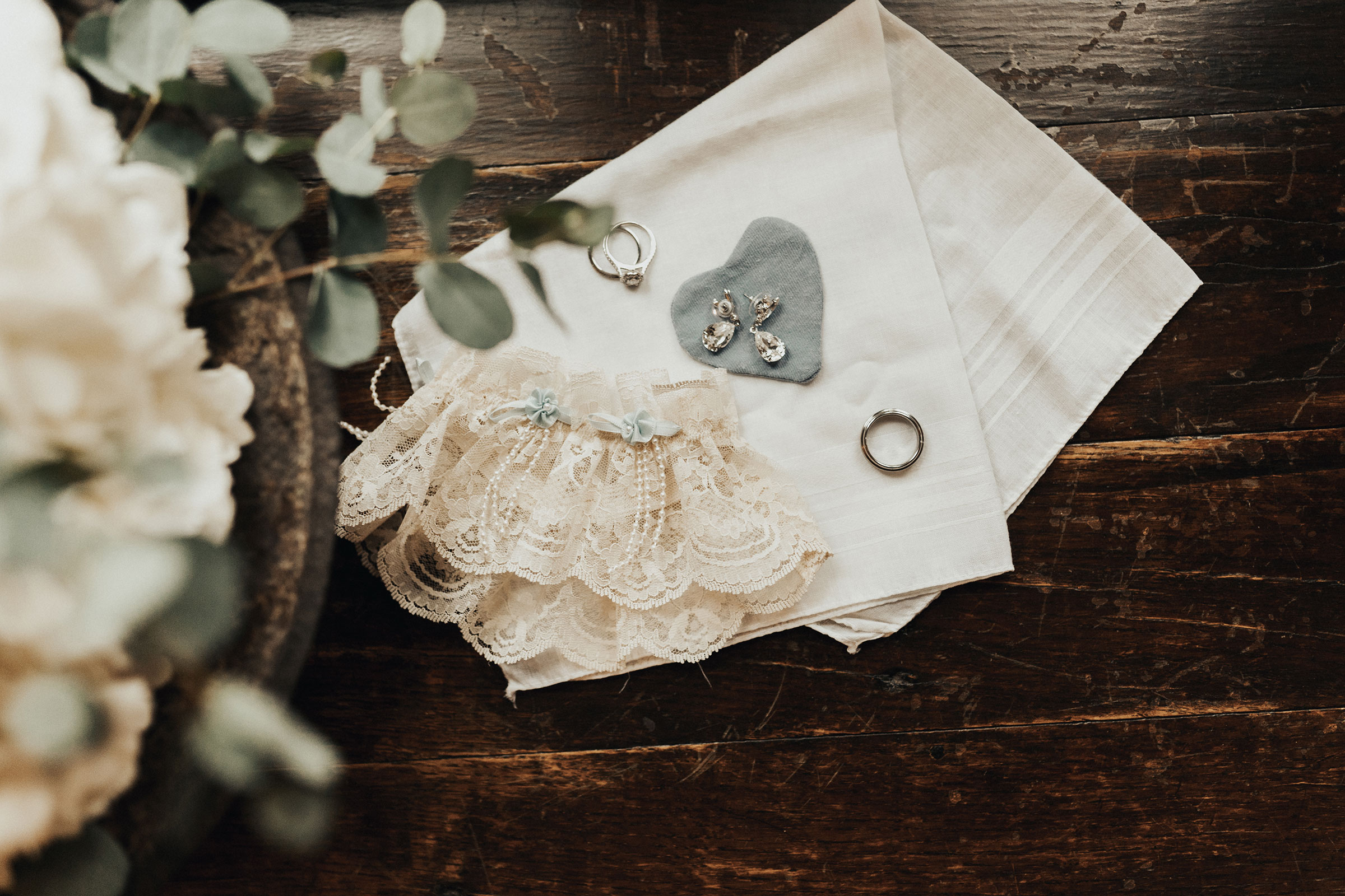 detail-shot-of-rings-bouquet-garter-and-earrings-elopement-salisbury-house-desmoines-iowa-raelyn-ramey-photography.jpg