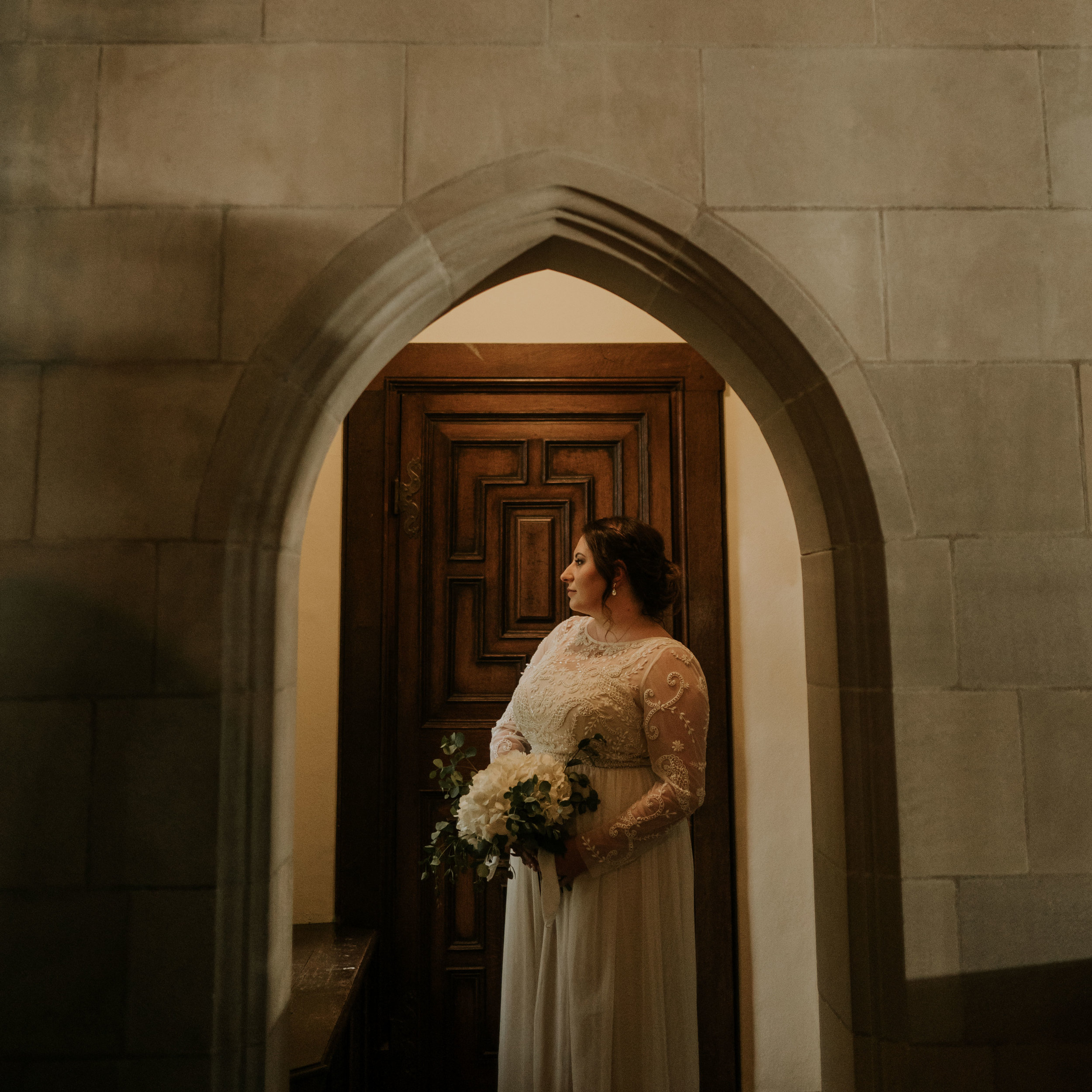 bride-standing-under-arch-looking-out-window-elopement-salisbury-house-desmoines-iowa-raelyn-ramey-photography.jpg