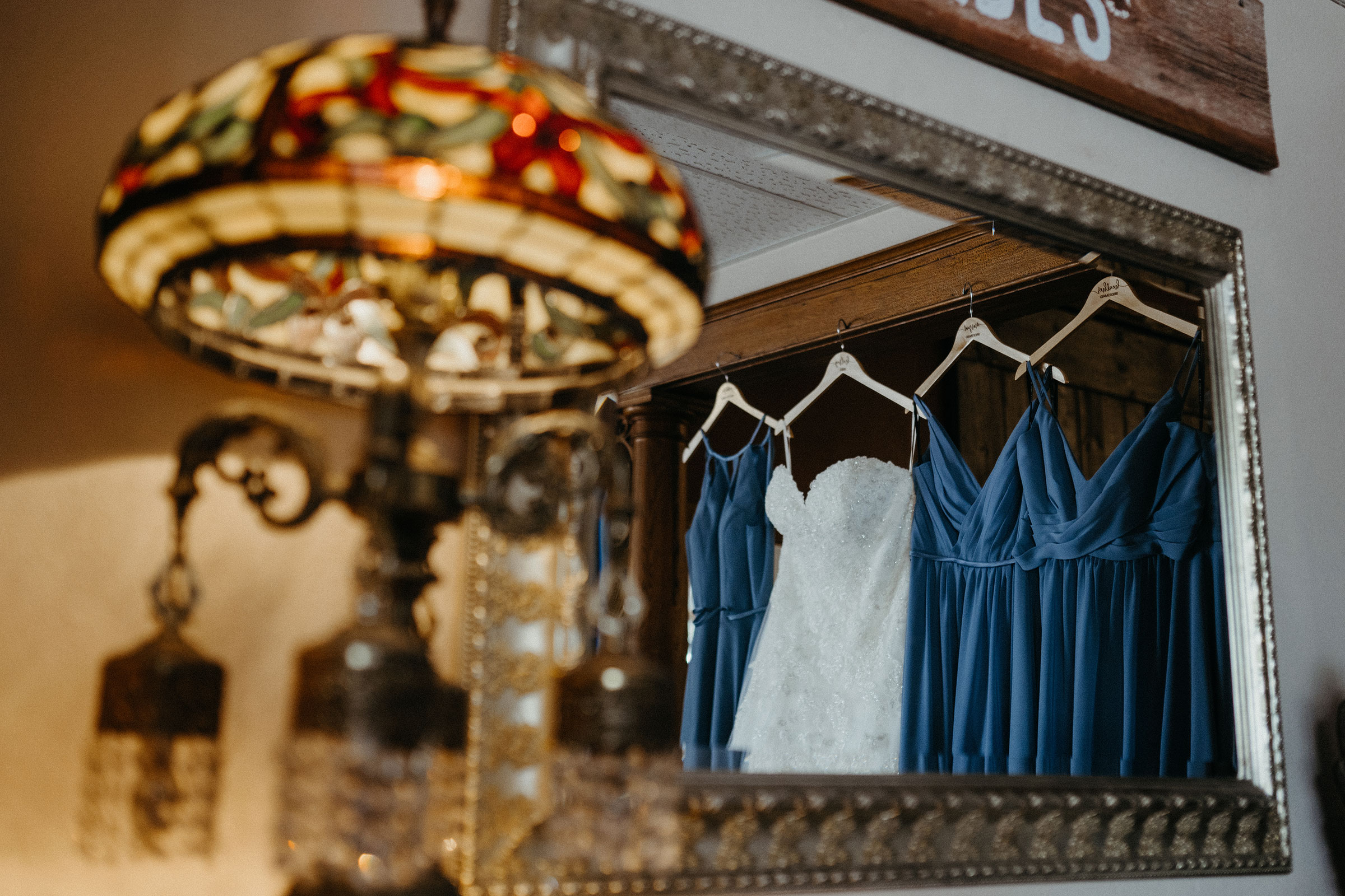 bridal-dress-and-bridesmaids-dresses-hanging-up-decades-event-center-building-desmoines-iowa-raelyn-ramey-photography..jpg