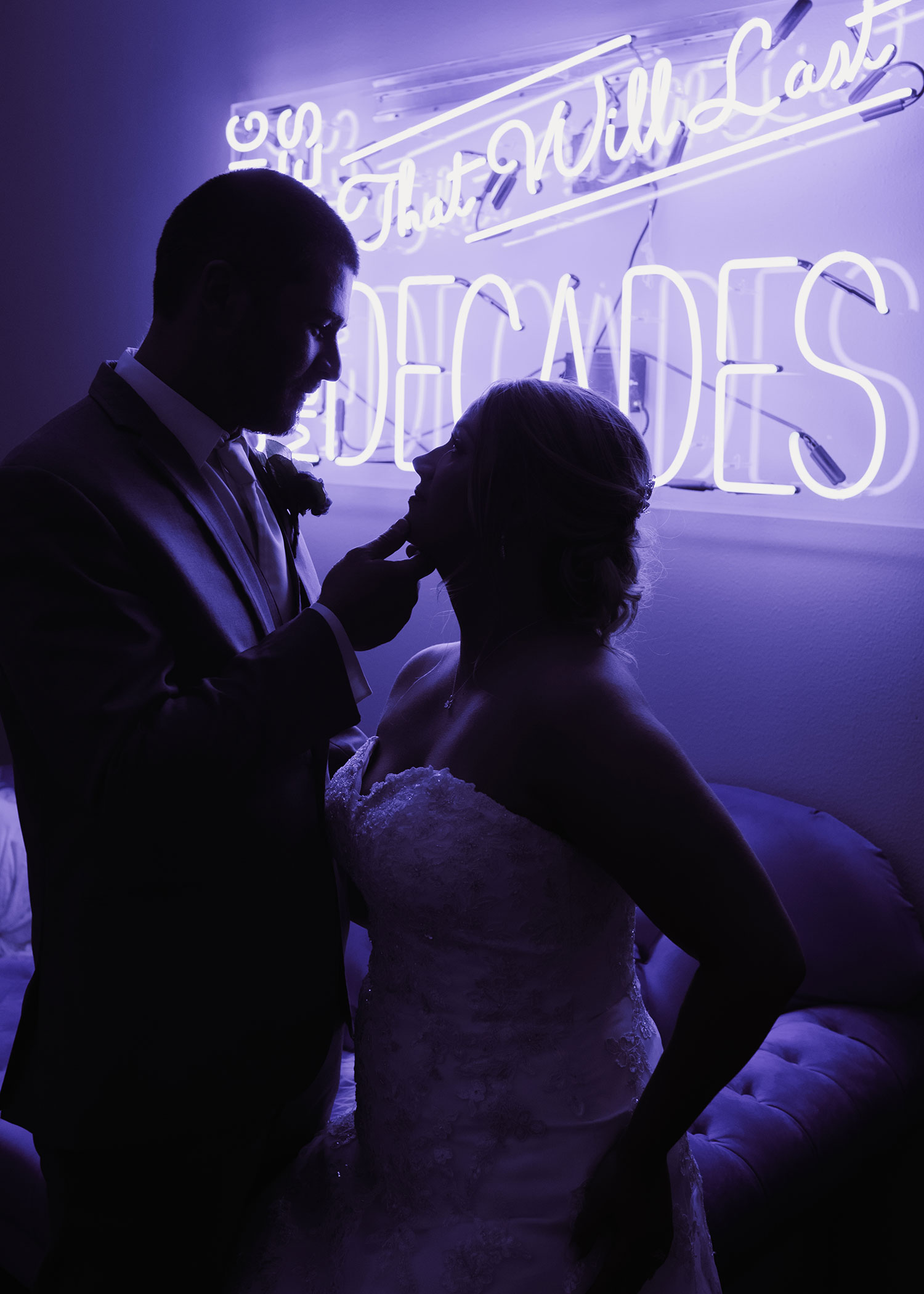 bride-and-groom-looking-at-each-other-in-front-of-neon-sign-decades-event-center-building-desmoines-iowa-raelyn-ramey-photography..jpg