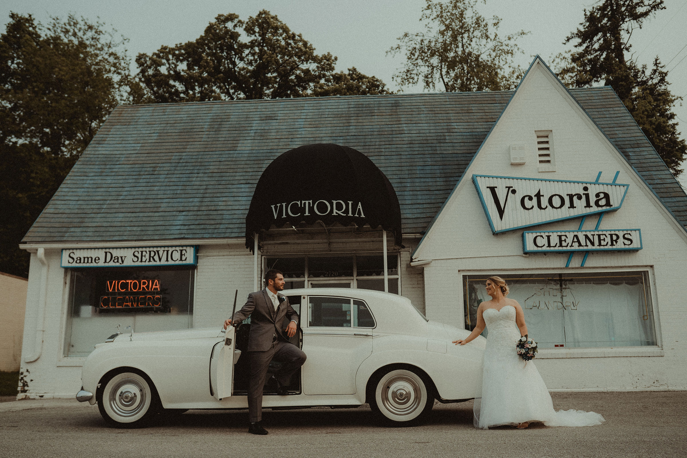 bride-and-groom-standing-outside-rollys-royce-in-front-of-victorias-cleaners-decades-event-center-building-desmoines-iowa-raelyn-ramey-photography..jpg