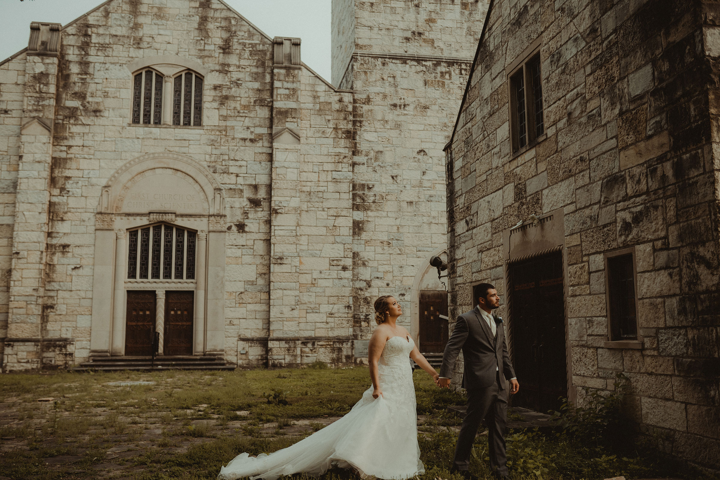 bride-and-groom-walking-around-old-church-decades-event-center-building-desmoines-iowa-raelyn-ramey-photography..jpg