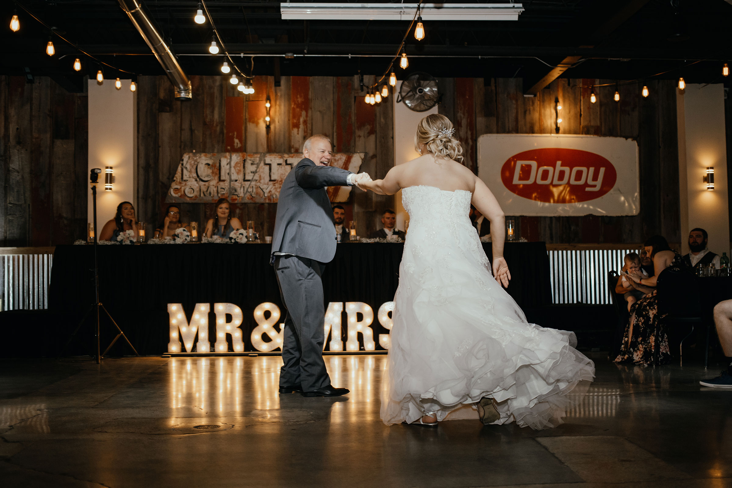 bride-dancing-father-decades-event-center-building-desmoines-iowa-raelyn-ramey-photography..jpg
