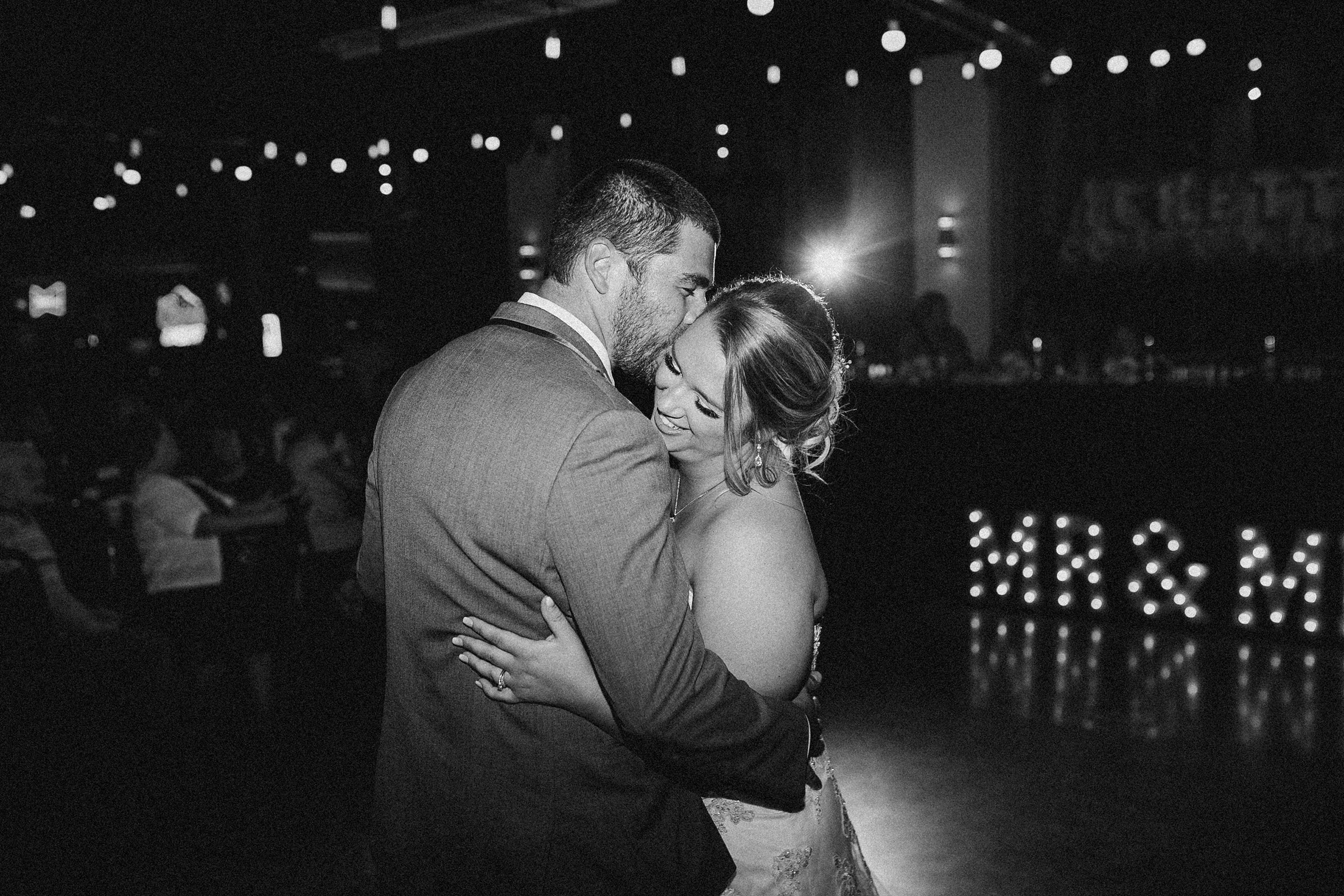 bride-dancing-with-groom-black-andw-white-decades-event-center-building-desmoines-iowa-raelyn-ramey-photography..jpg