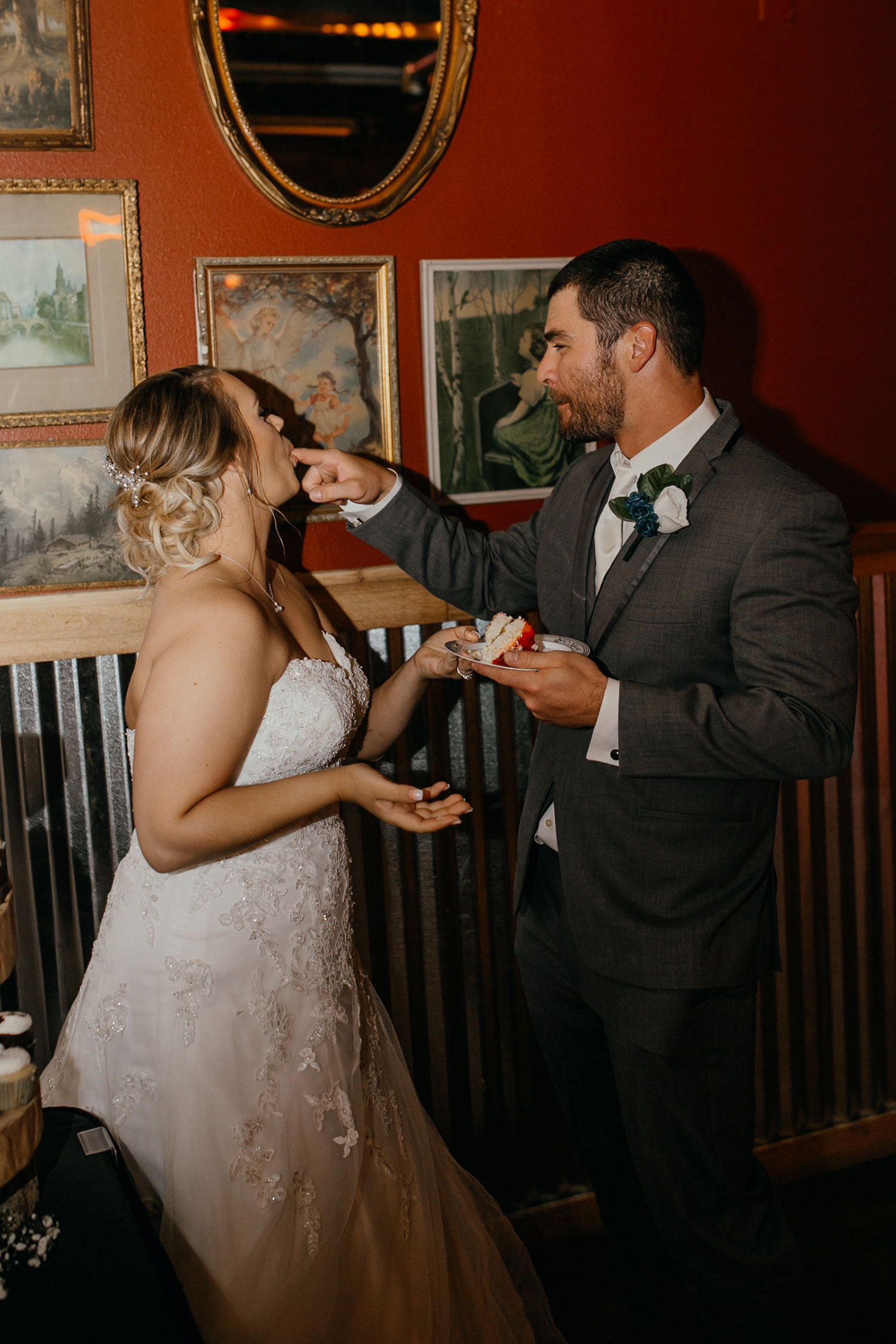bride-eating-cheese-cake-off-groom-finger-decades-event-center-building-desmoines-iowa-raelyn-ramey-photography..jpg
