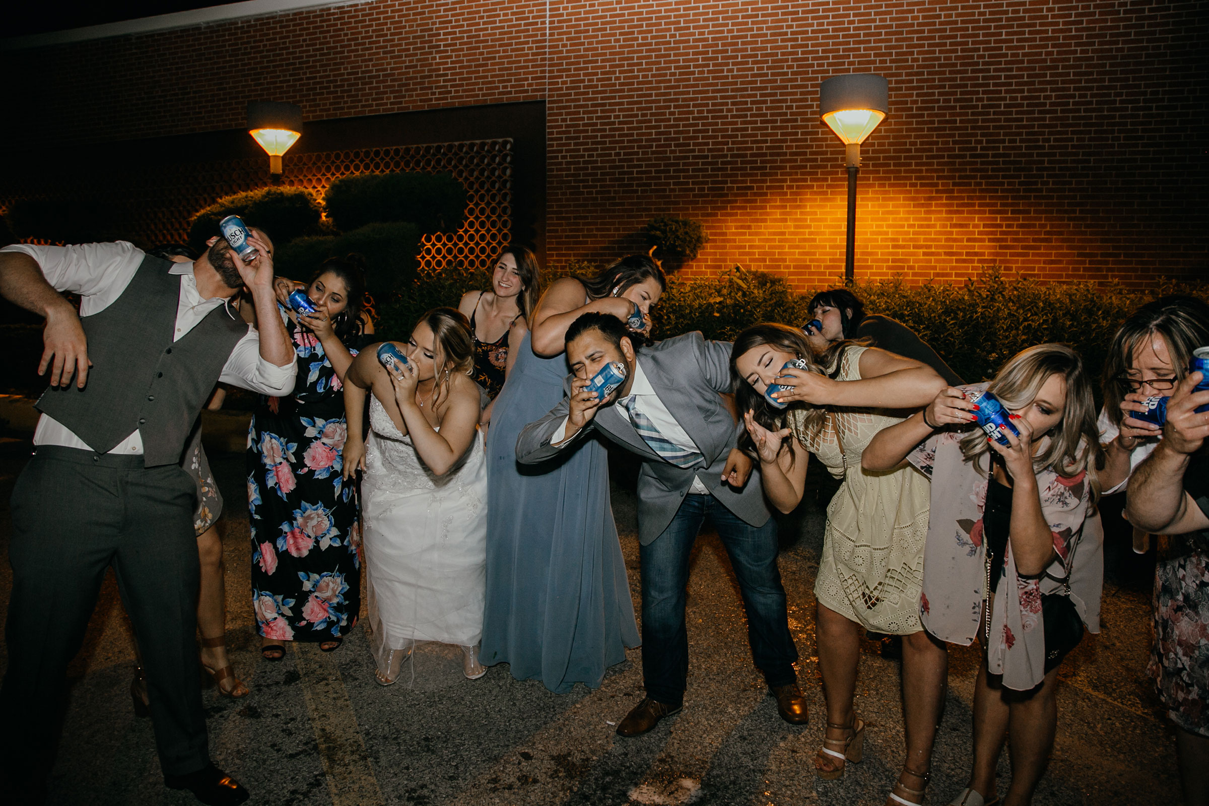 bride-groom-and-guests-shotgun-beers-decades-event-center-building-desmoines-iowa-raelyn-ramey-photography..jpg