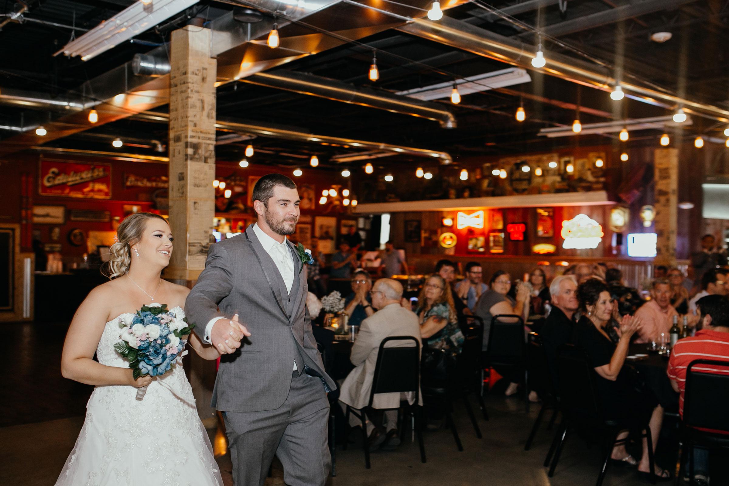 bride-groom-enterance-holding-hands-decades-event-center-building-desmoines-iowa-raelyn-ramey-photography..jpg