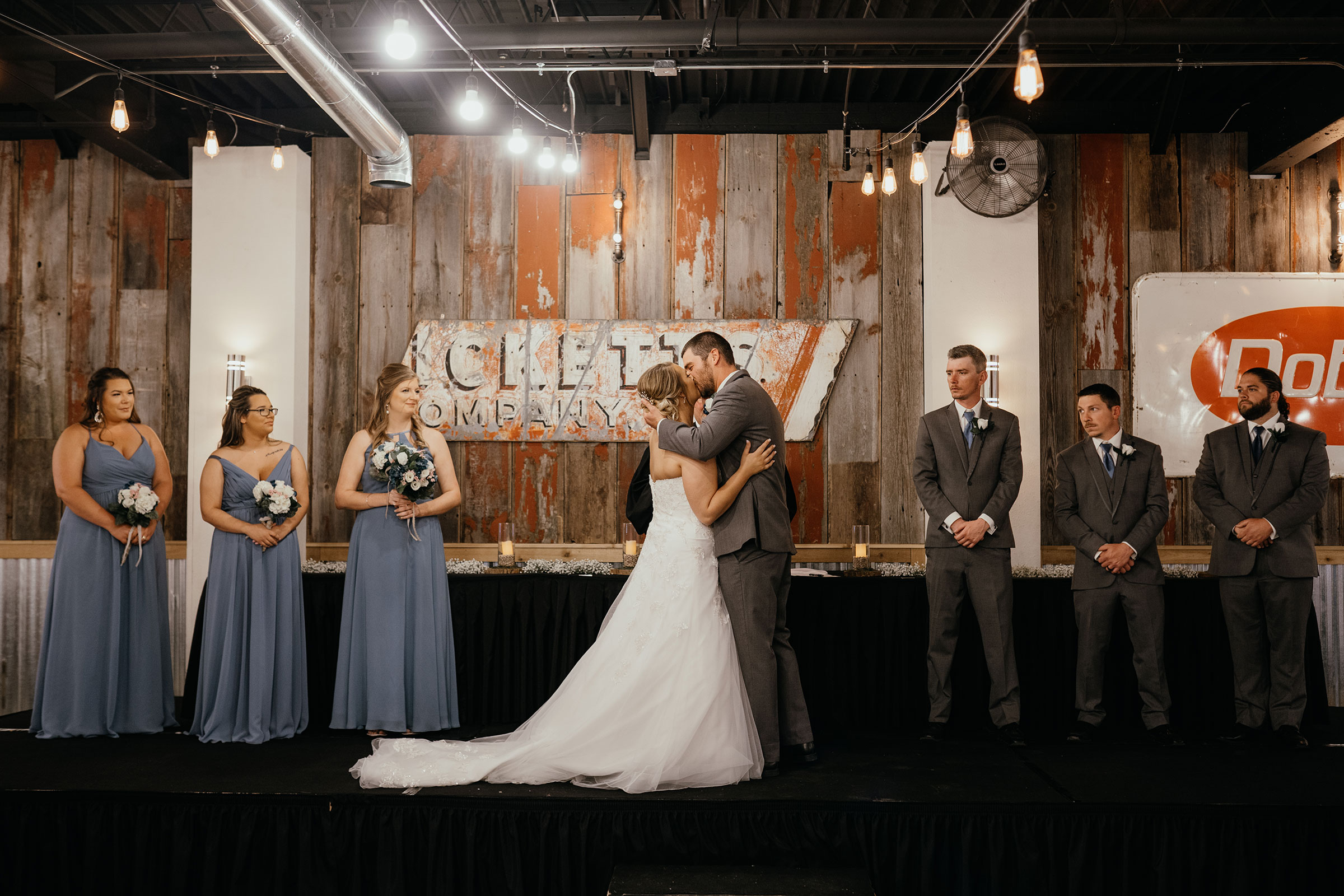 bride-groom-first-kiss-at-ceremony-decades-event-center-building-desmoines-iowa-raelyn-ramey-photography..jpg