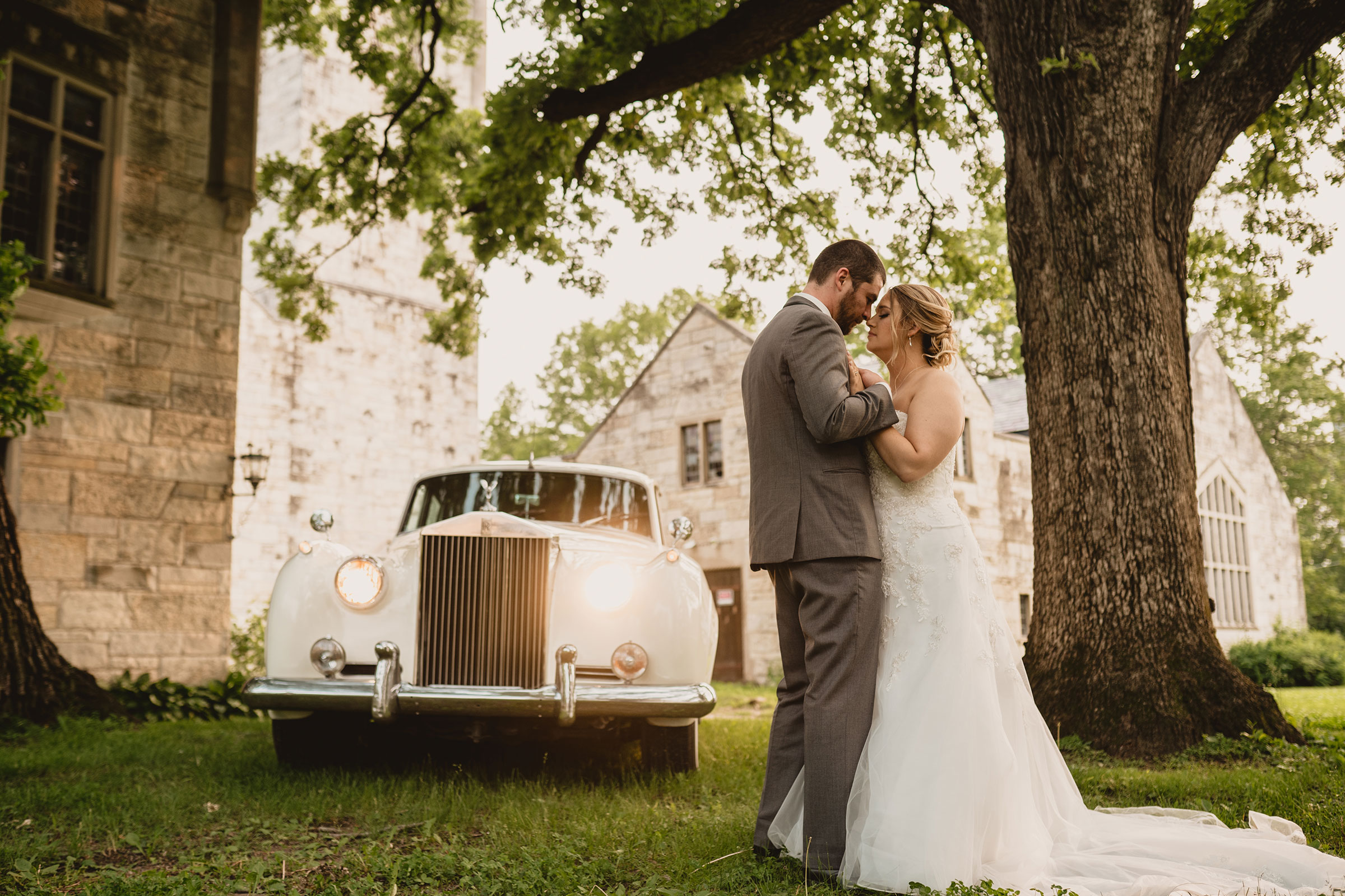 bride-groom-holding-each-other-while-standing-in-front-of-rolls-royce-decades-event-center-building-desmoines-iowa-raelyn-ramey-photography..jpg