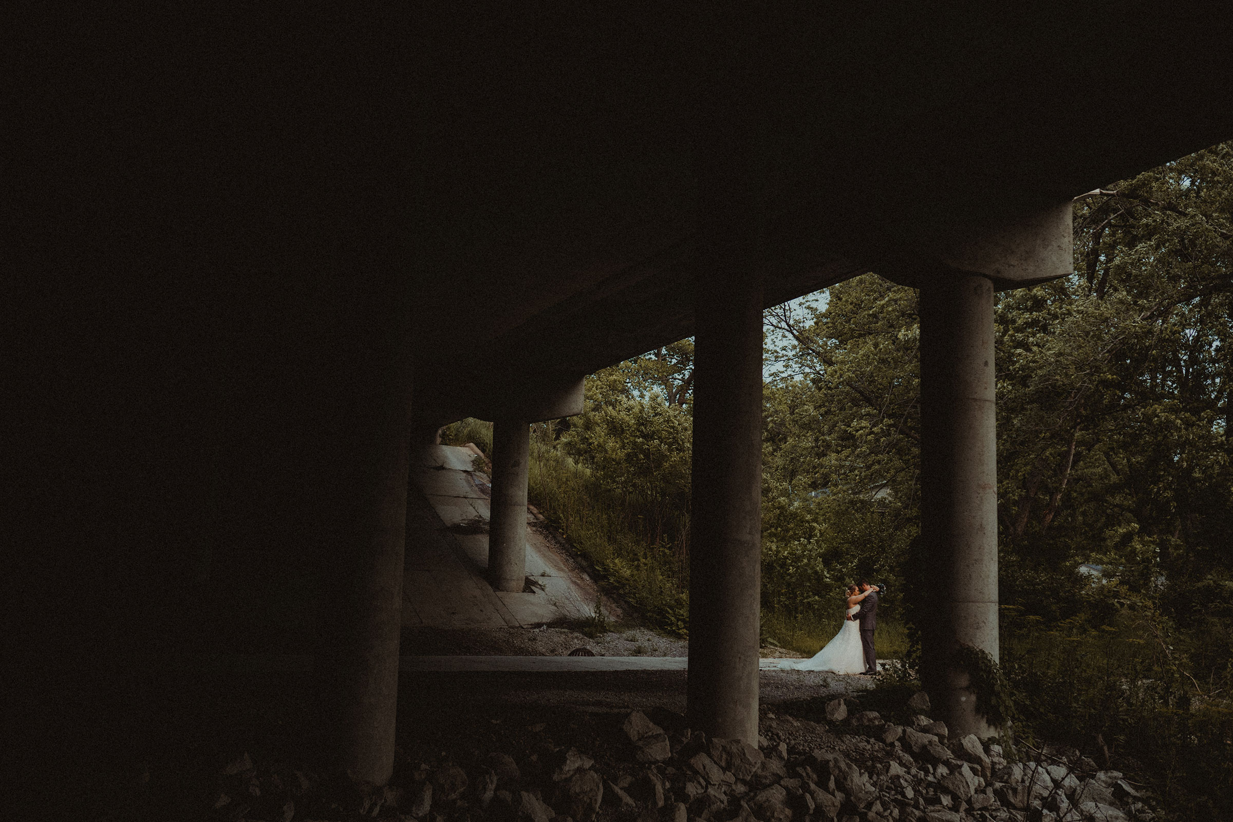 bride-groom-hugging-by-overpass-decades-event-center-building-desmoines-iowa-raelyn-ramey-photography..jpg