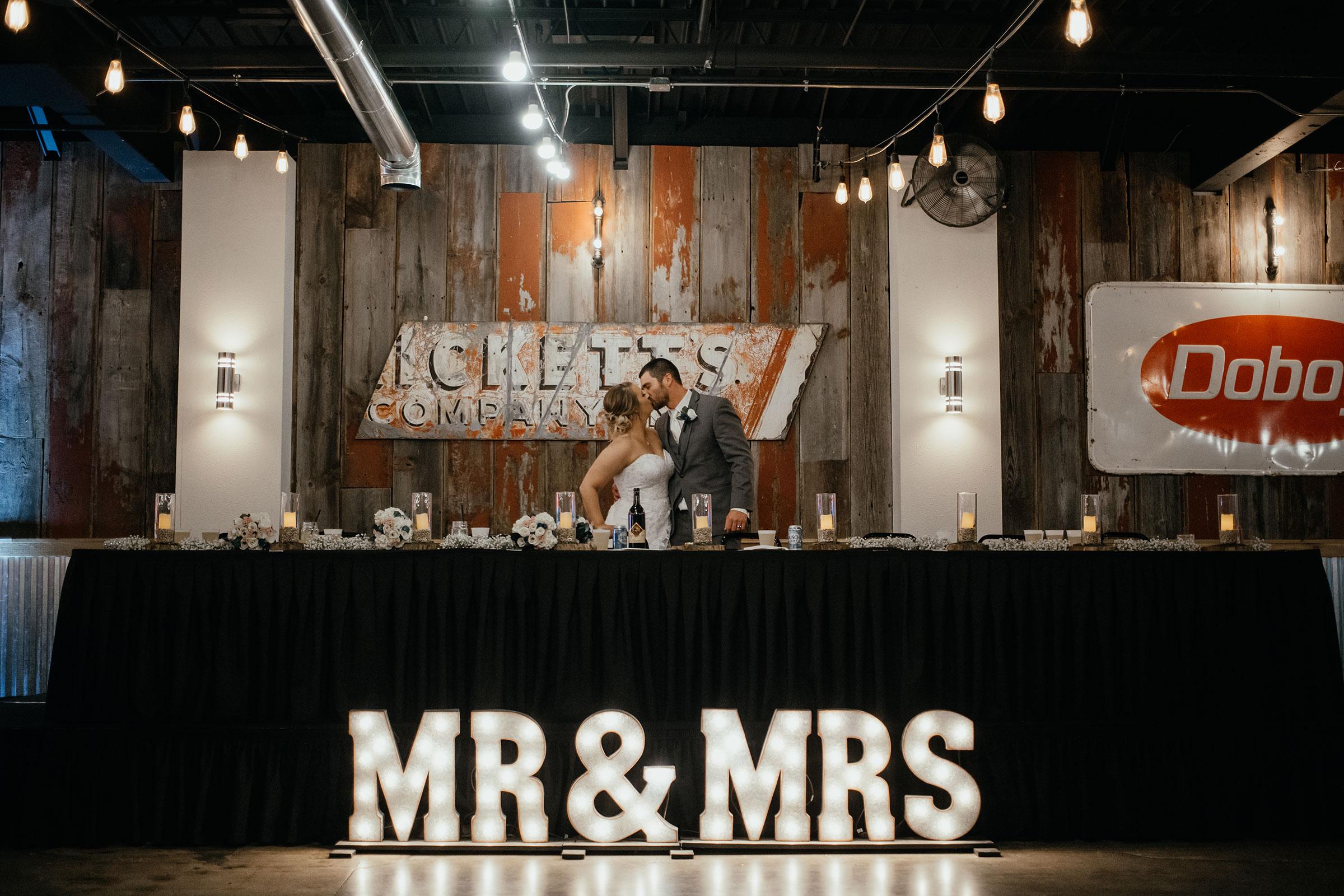 bride-groom-kissing-at-head-table-decades-event-center-building-desmoines-iowa-raelyn-ramey-photography..jpg