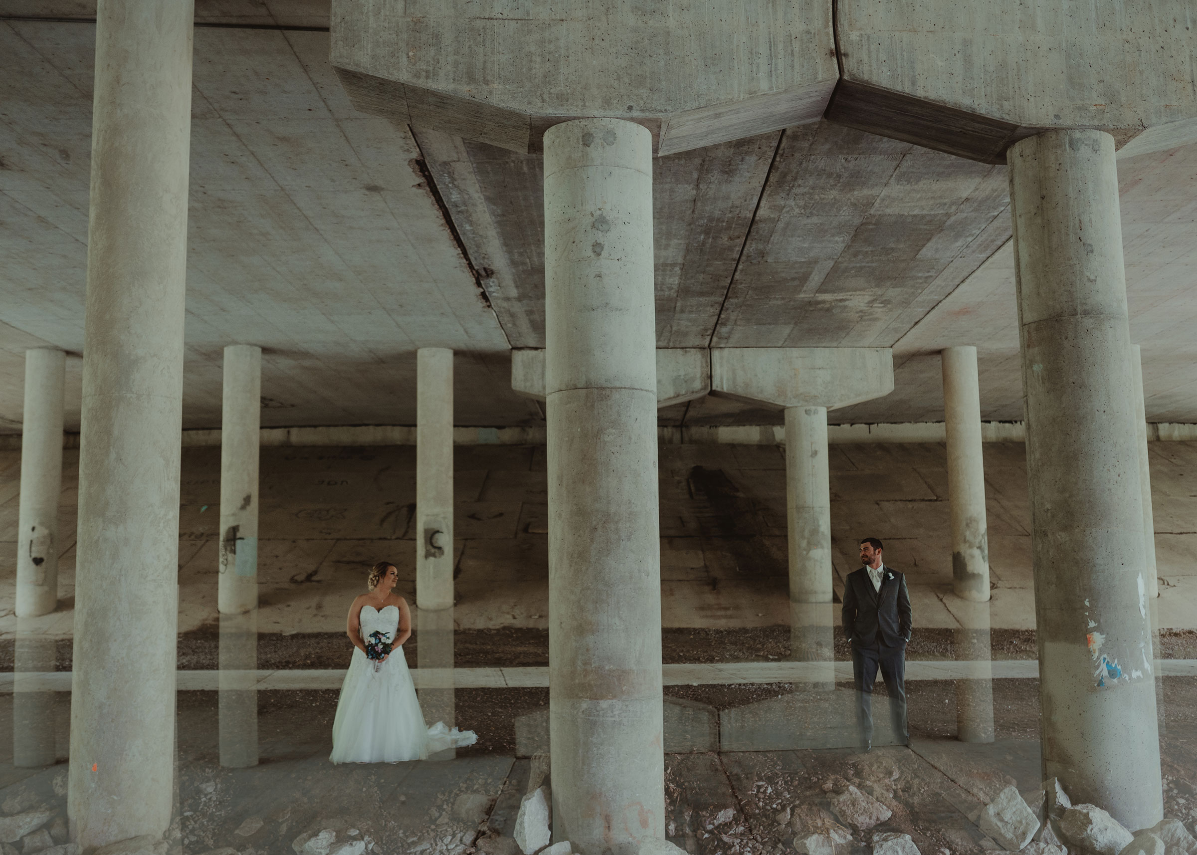 bride-groom-standing-under-overpass-decades-event-center-building-desmoines-iowa-raelyn-ramey-photography..jpg