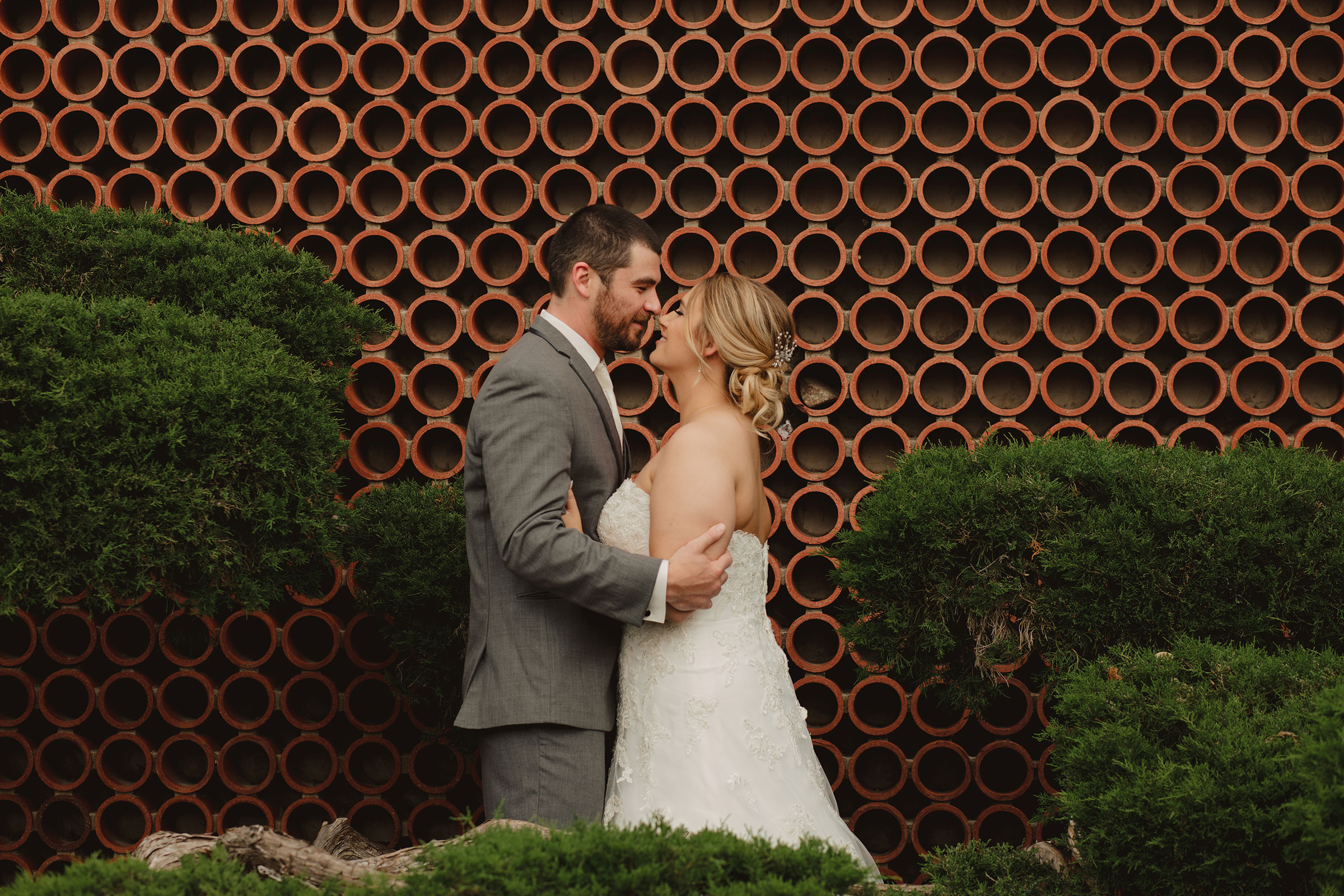 bride-groom-looking-in-eyes-in-front-of-circle-wall-decades-event-center-building-desmoines-iowa-raelyn-ramey-photography..jpg
