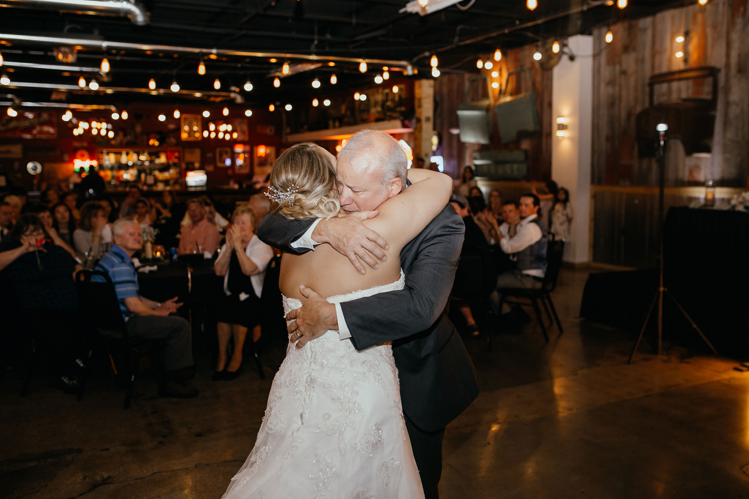 bride-hugging-father-at-dance-decades-event-center-building-desmoines-iowa-raelyn-ramey-photography..jpg