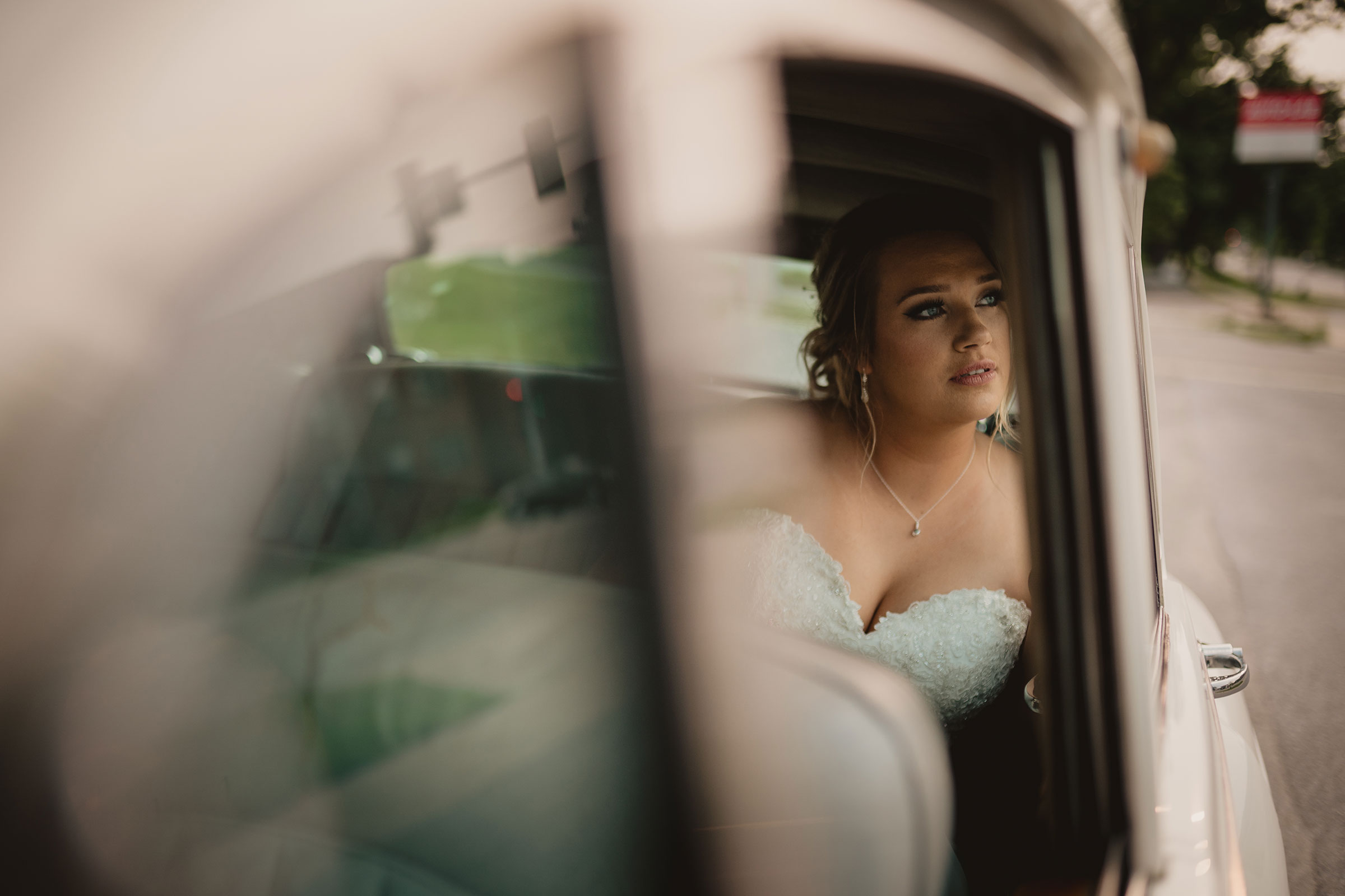 bride-looking-out-rolls-royce-window-decades-event-center-building-desmoines-iowa-raelyn-ramey-photography.jpg