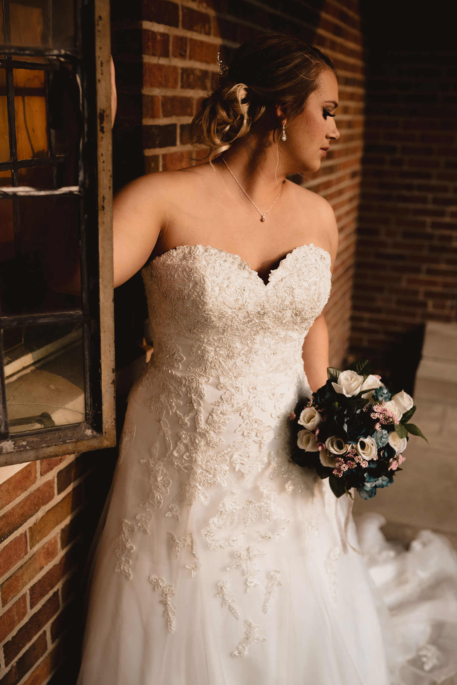 bride-portrait-standing-next-to-brick-in-sunlight-decades-event-center-building-desmoines-iowa-raelyn-ramey-photography..jpg