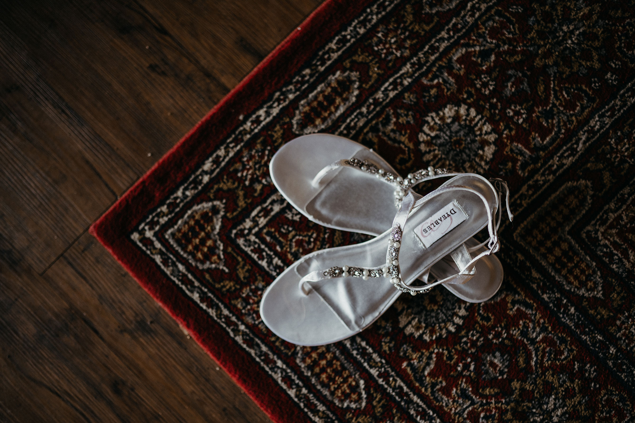 bride-shoes-on-old-rug-decades-event-center-building-desmoines-iowa-raelyn-ramey-photography..jpg