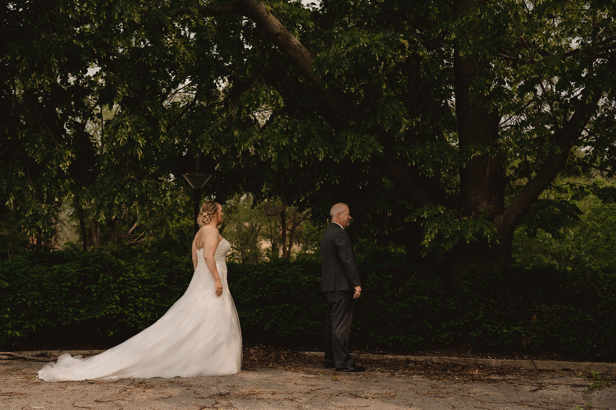 bride-walking-to-dad-for-first-look-decades-event-center-building-desmoines-iowa-raelyn-ramey-photography..jpg